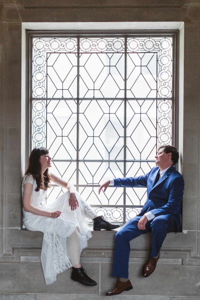newlywed couple reclining in 3rd floor windowsills at san francisco city hall