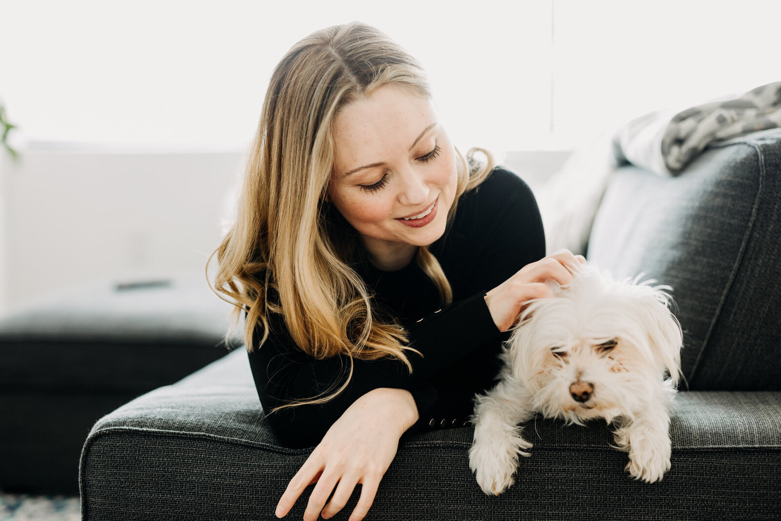 woman with white dog on couch