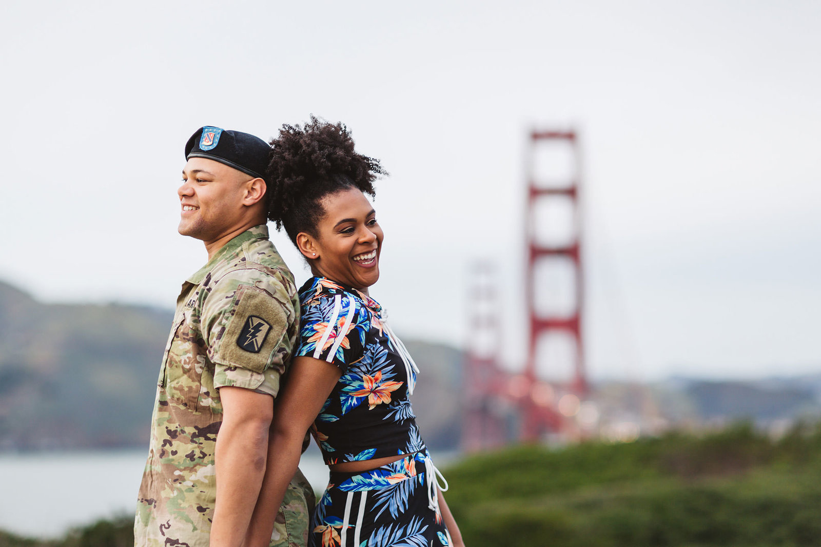 dancing meets military theme for this couple standing back to back with the golden gate bridge behind them