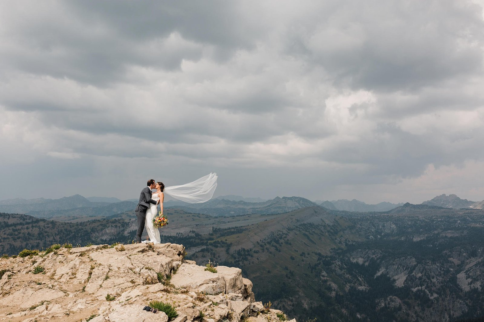 A bride and groom embrace with a romantic kiss on top of a mountain during their adventure elopement in Jackson Hole