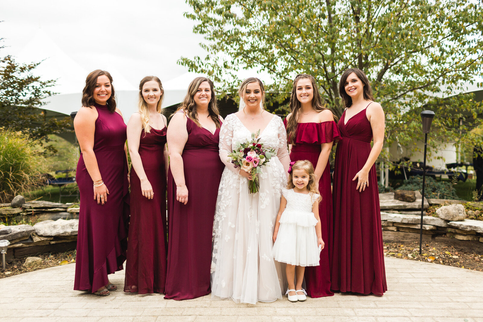 bridal party smiling for portrait at rustic wedding with burgandy dresses ohio