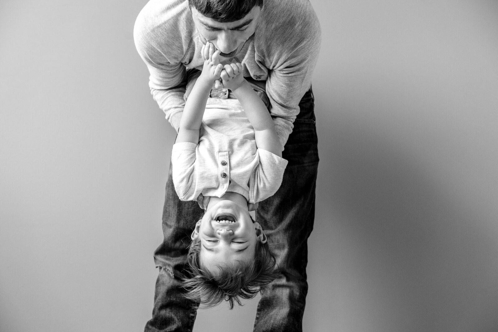 Son giggling as dad hangs him upside down