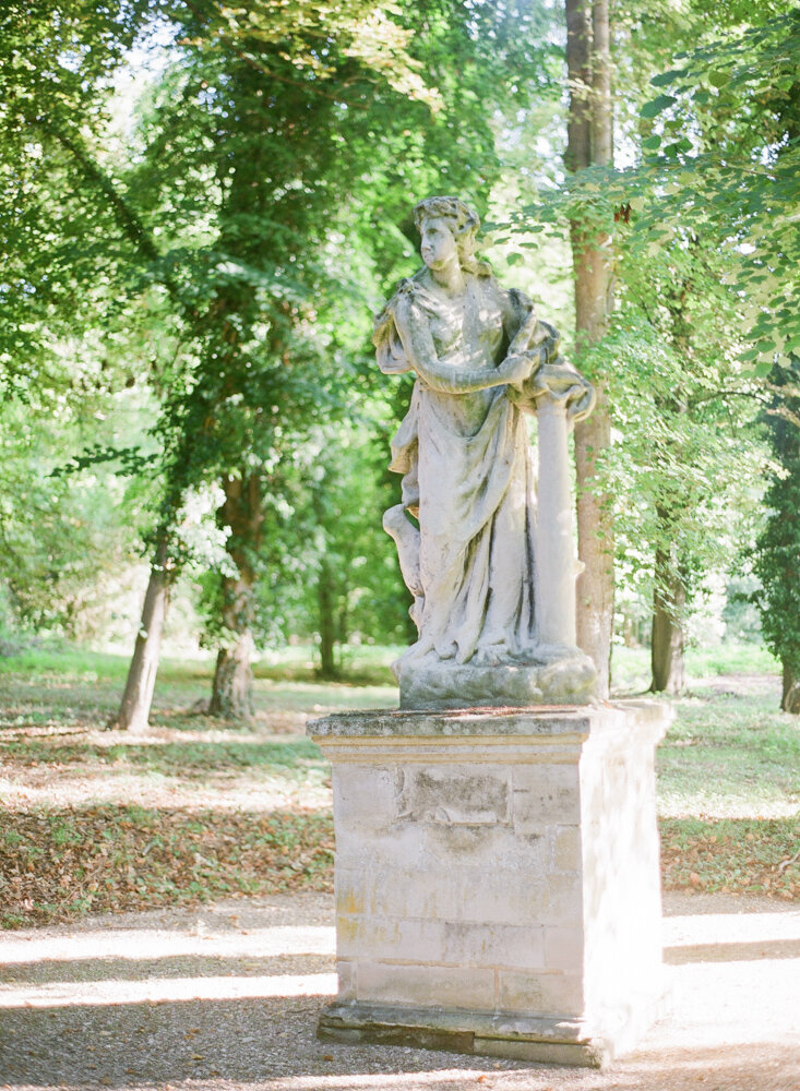 Large marble statue sitting in French parkland