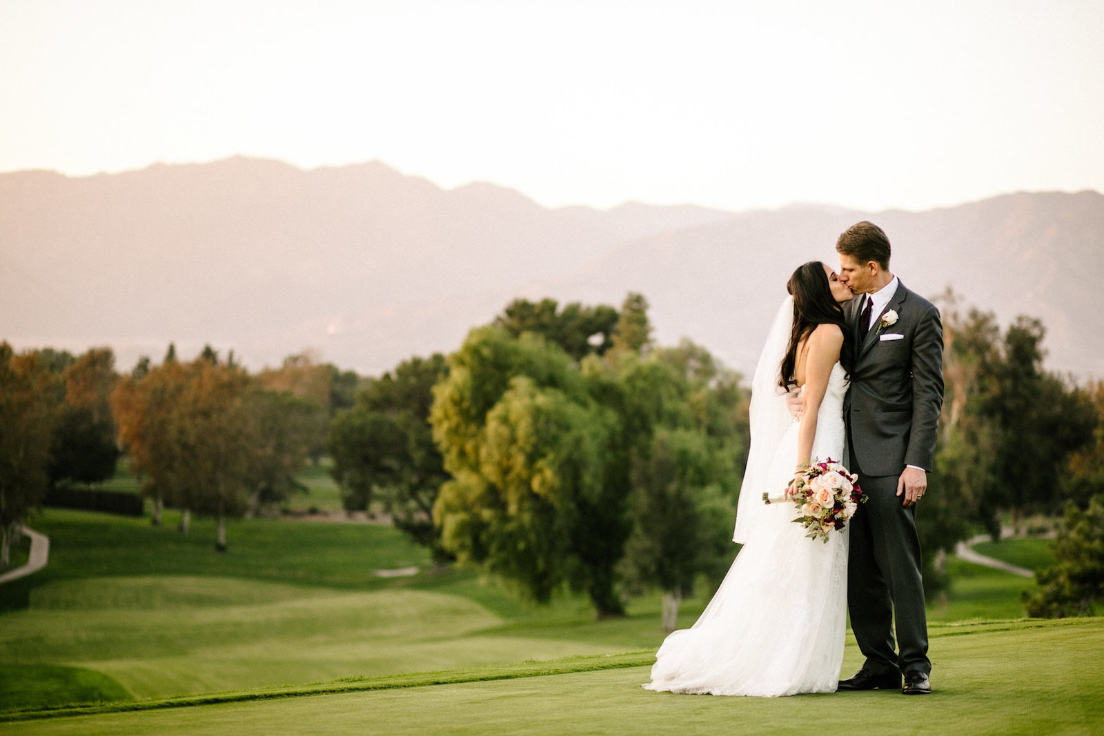 bride and groom kissing at red hill country club wedding in rancho cucamonga