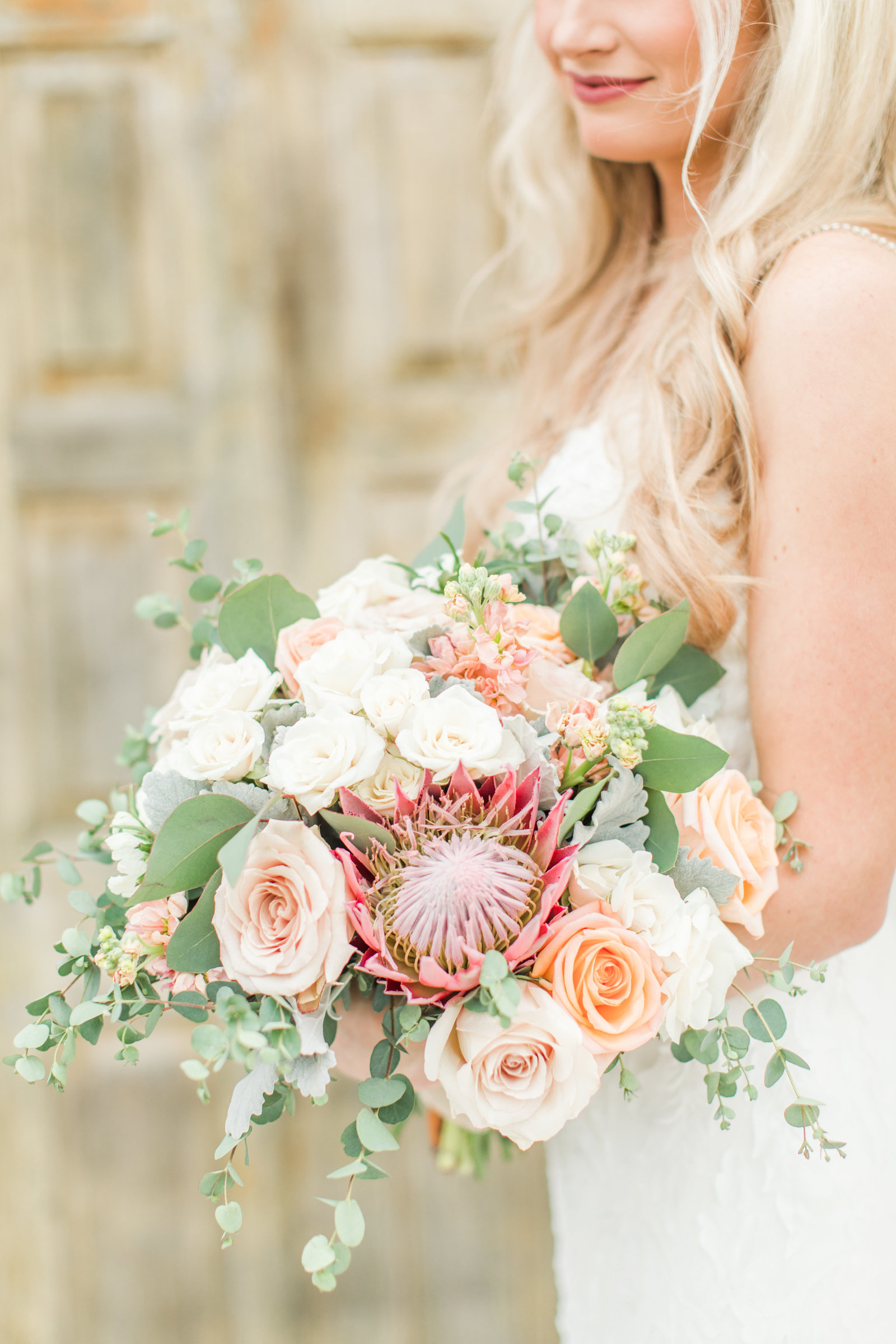 Bouquet with peach roses and pink proteas