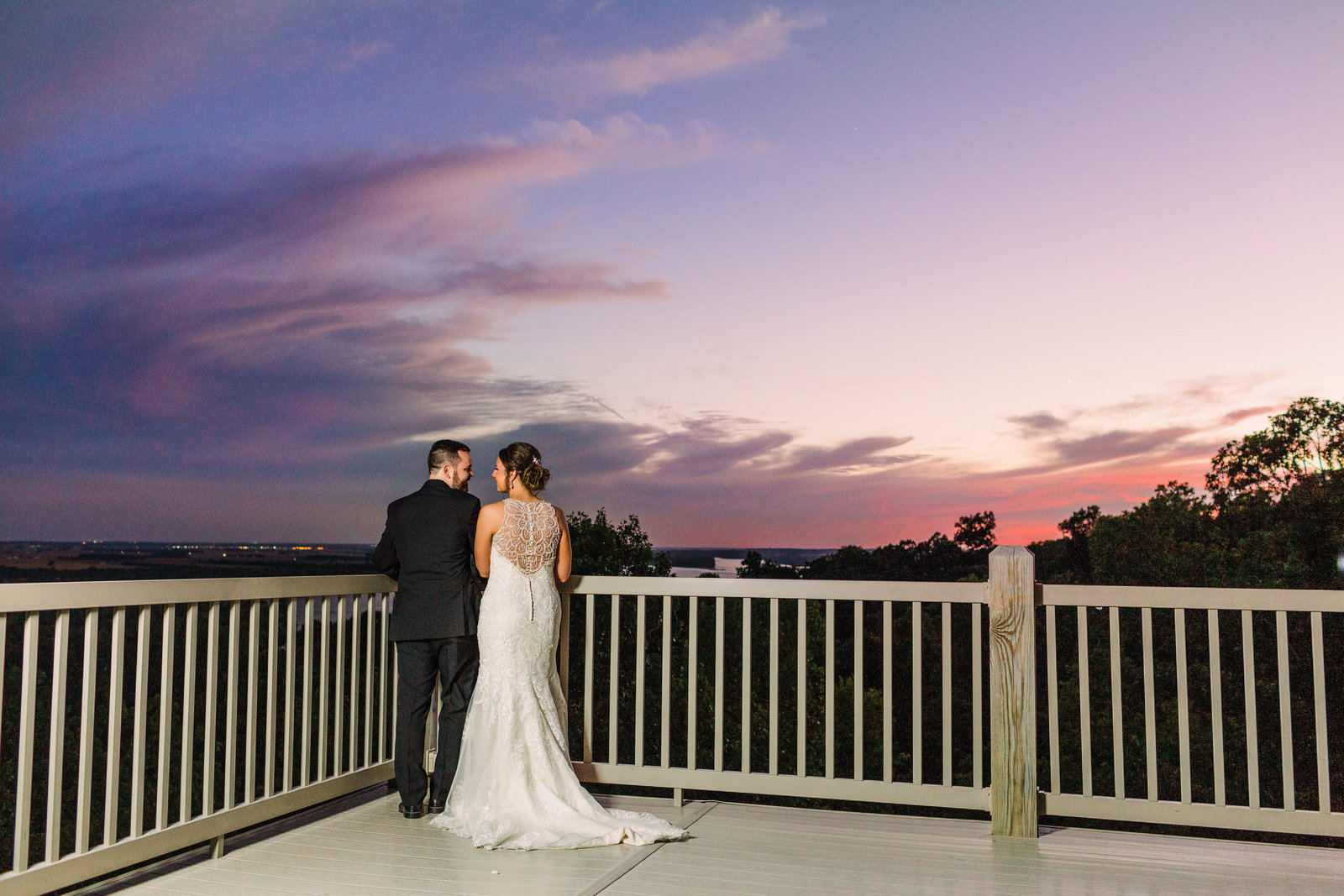 Bride and Groom, Courtney and Daniel, stand looking at a sunset on the Aeries Winery balcony by Jackelynn Noel Photography