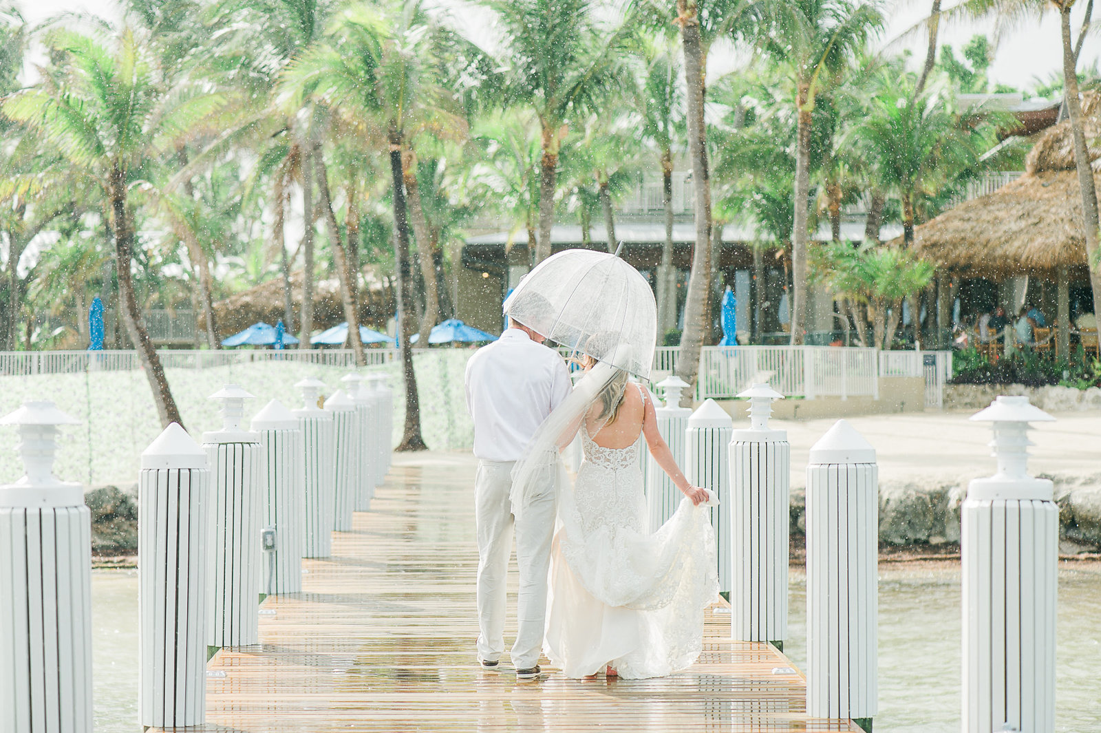 Couple on Pier in rain - Cheeca Wedding - Palm Beach Wedding Photography by Palm Beach Photography, Inc.