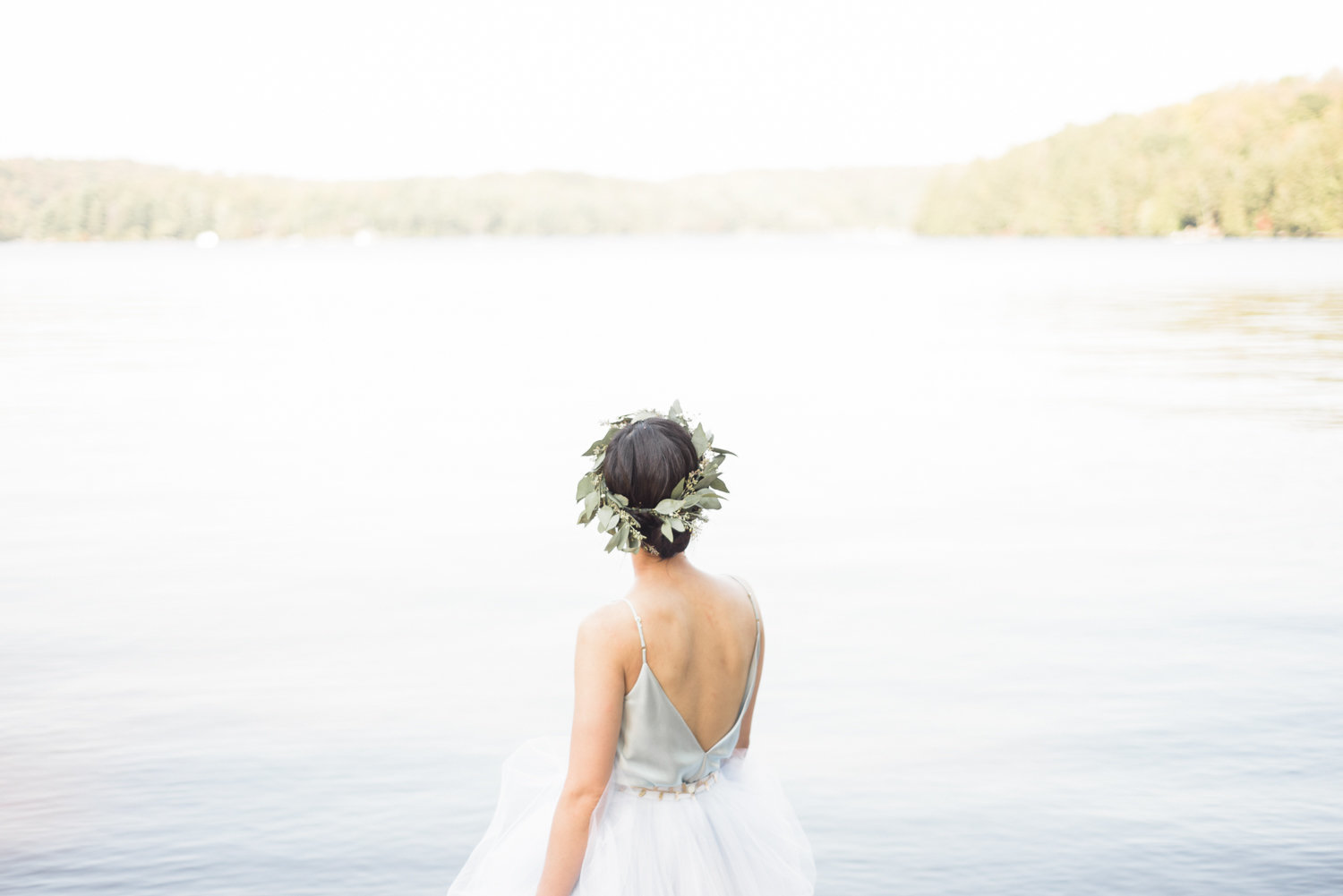 Bride with green flower crown looking out at a lake in Muskoka