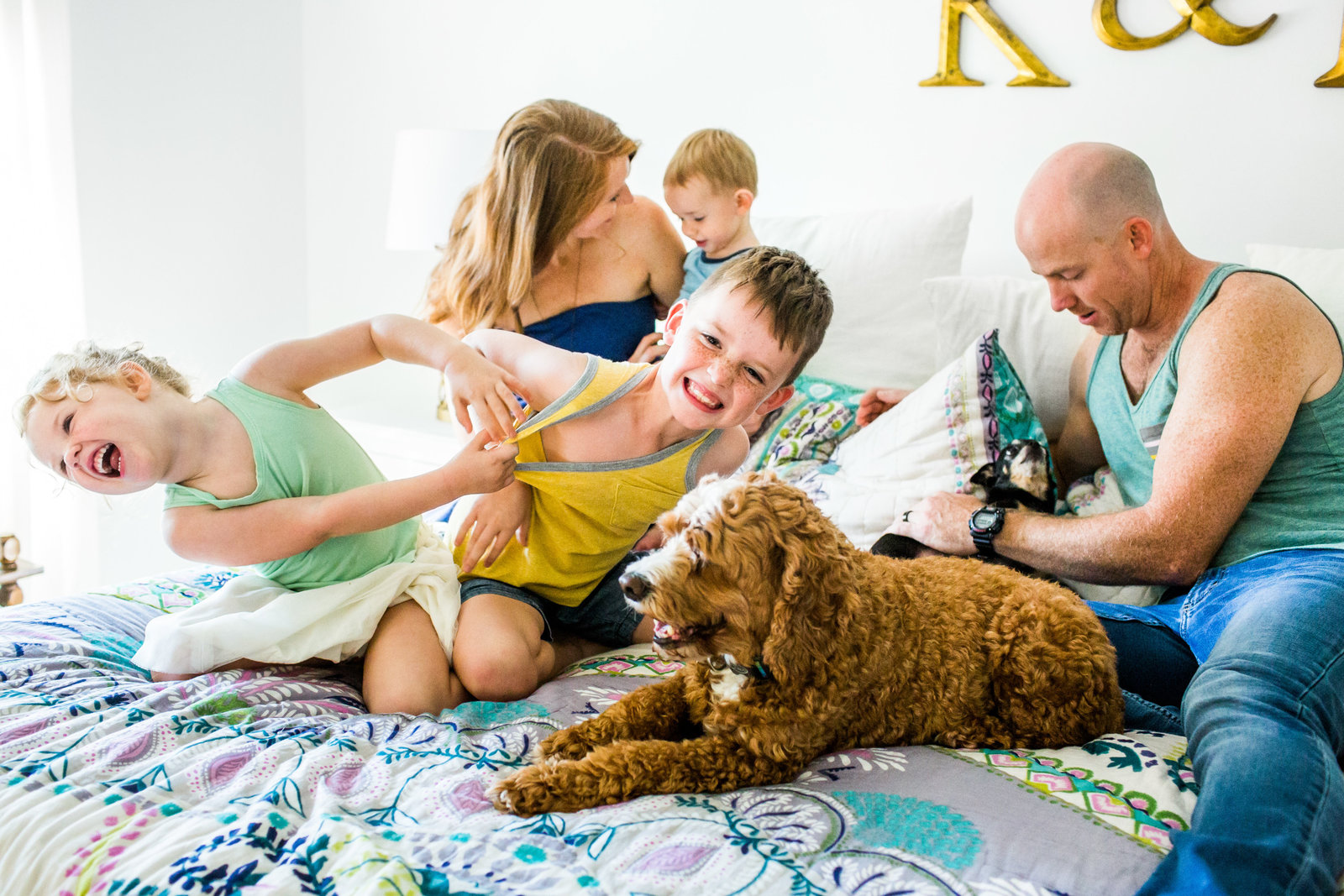 Family playing on the bed for in home portrait session