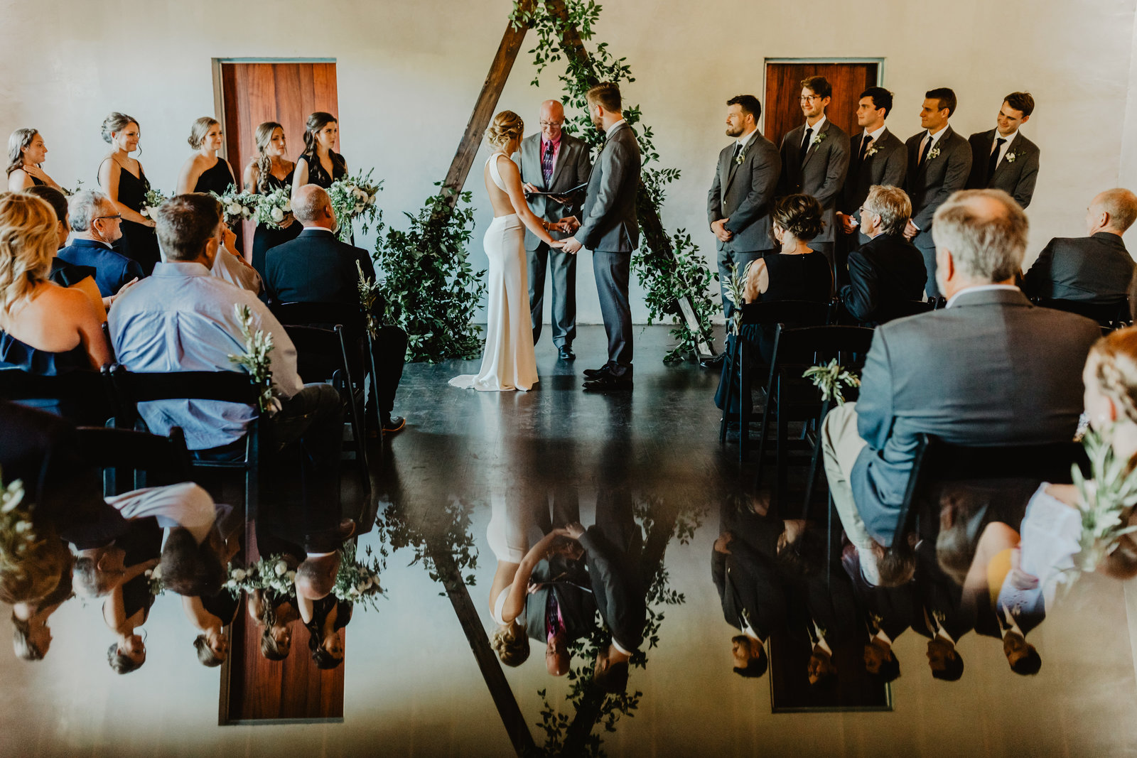 Bride and Groom stand at alter in front of guests with them being reflected at The Ruby