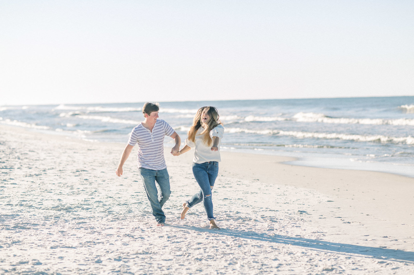 Couple running on the beach captured by Staci Addison Photography