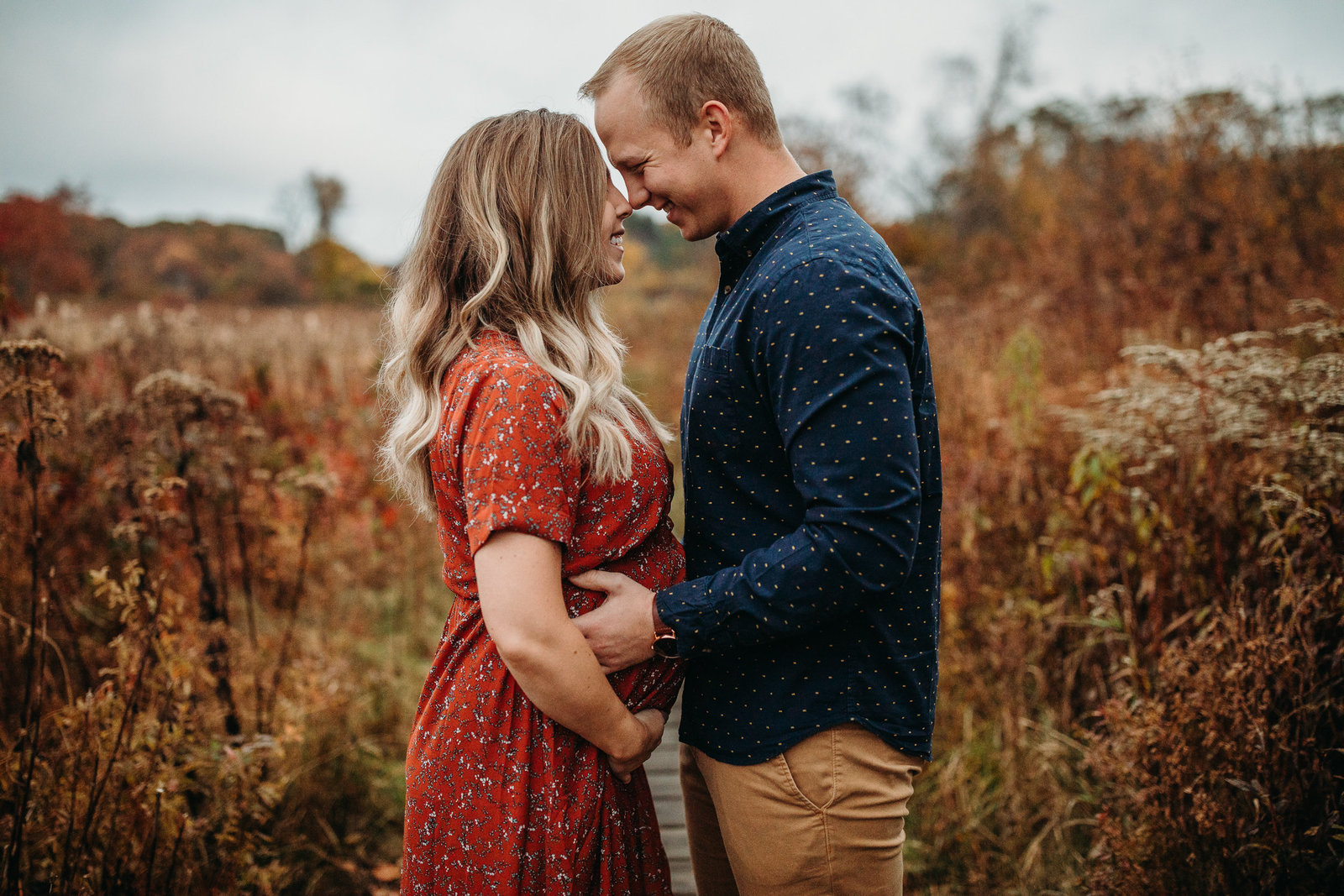 expectant couple stands nose to nose in autumn maternity photoshoot