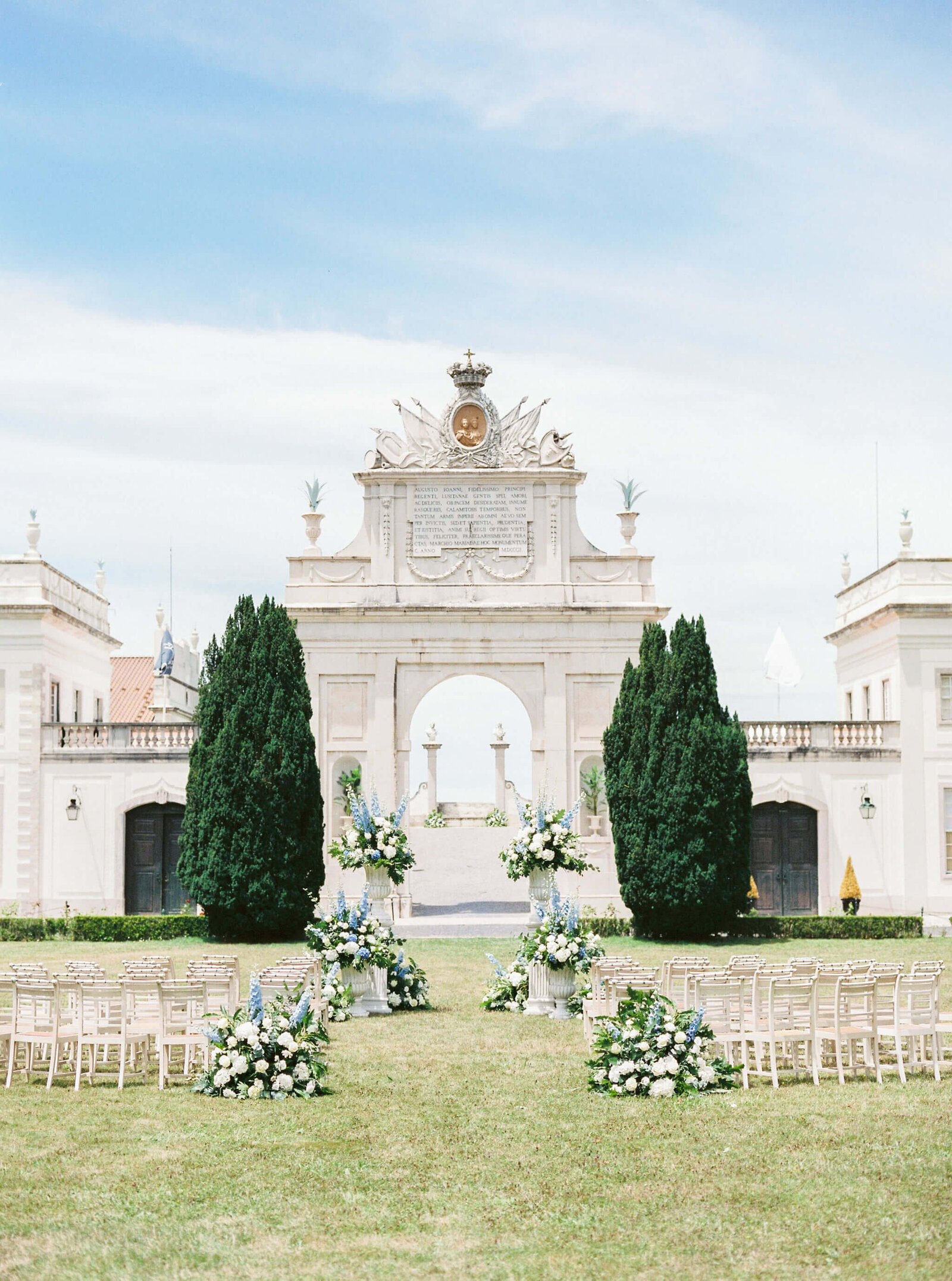 Wedding ceremony in tons of white and blue at Seteais Palace arch wedding