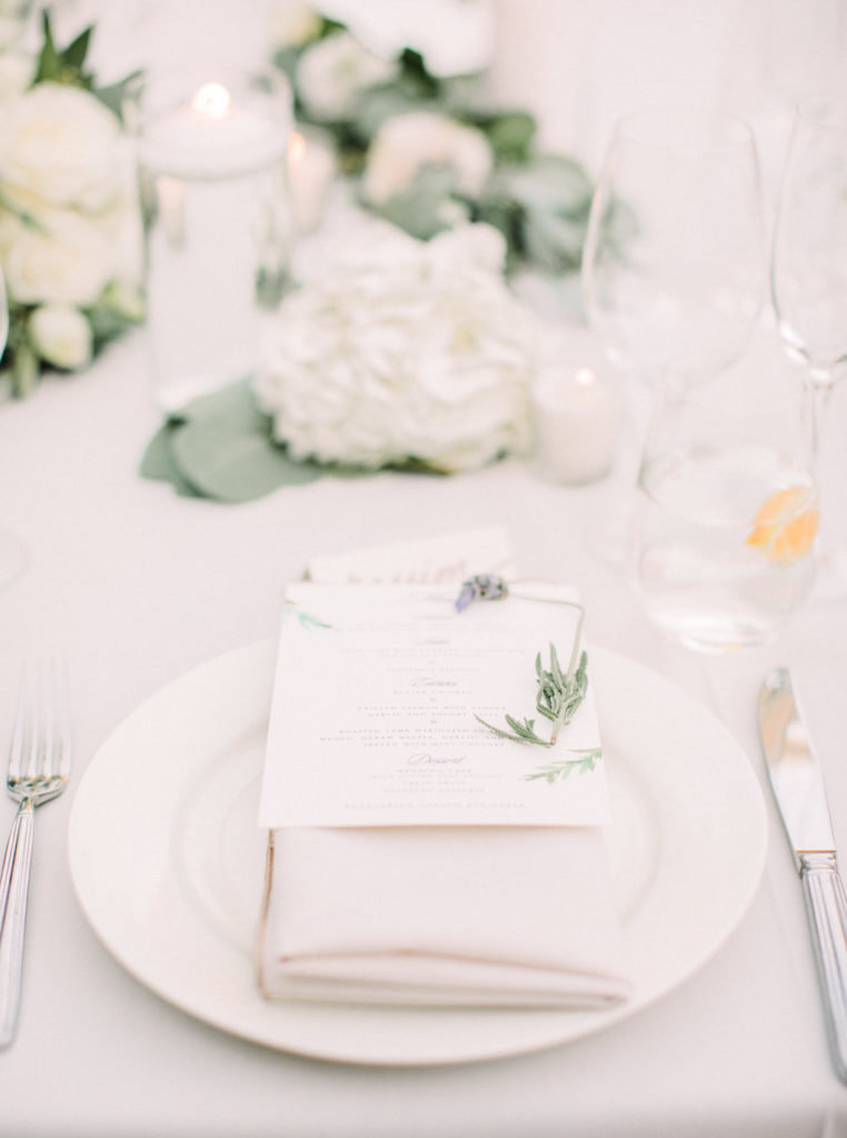 Simple and classic wedding reception table setting with menu card and white floral centerpieces at this Butterfly Lane Estate wedding in Montecito