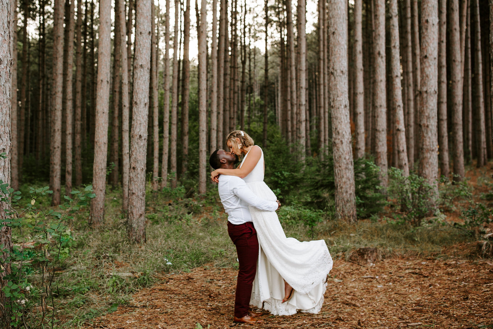 Couple kissing in tall timber trees at Pinewood Wedding Venue