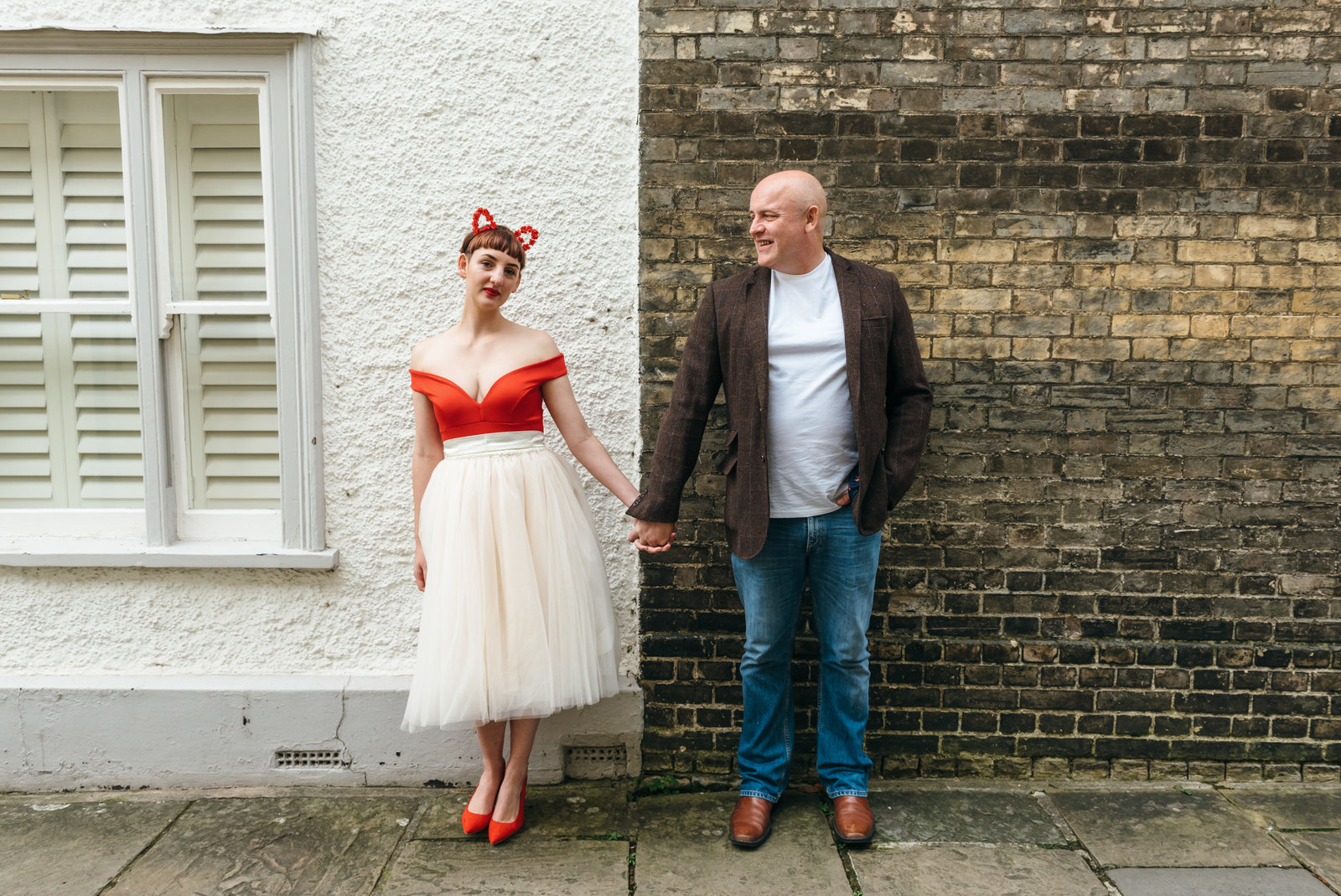 Lisa and Neil stand in front of a brick wall in Norwich. and hold hands. Lisa is looking at the camera and Neil is looking at Lisa and smiling.