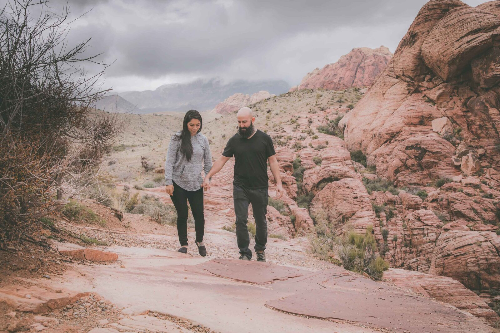 Couple walks on red rocks among amazing views.