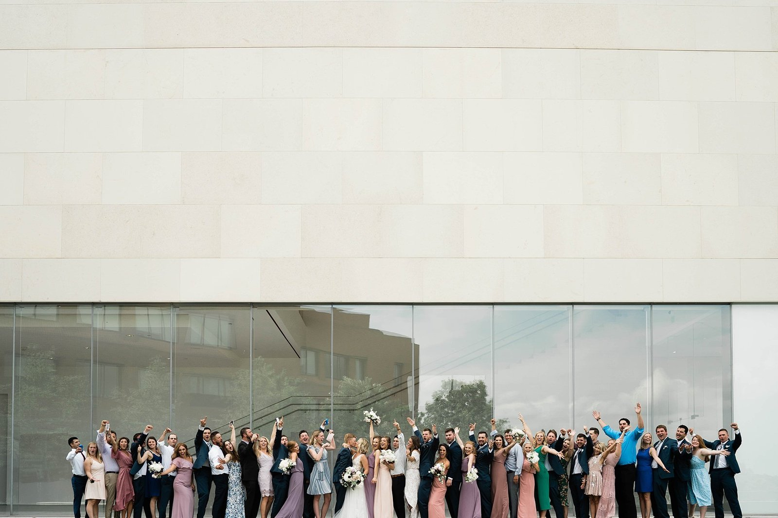 Large wedding party celebrates in front of Nerman Museum