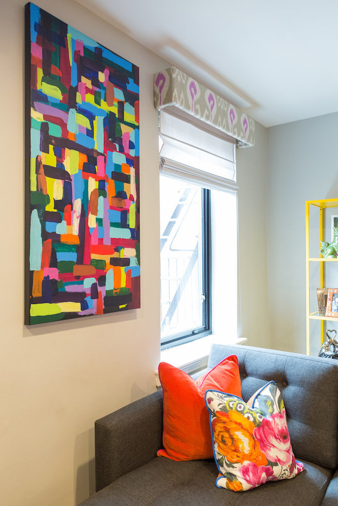 A colorful abstract painting hung above a gray sectional.