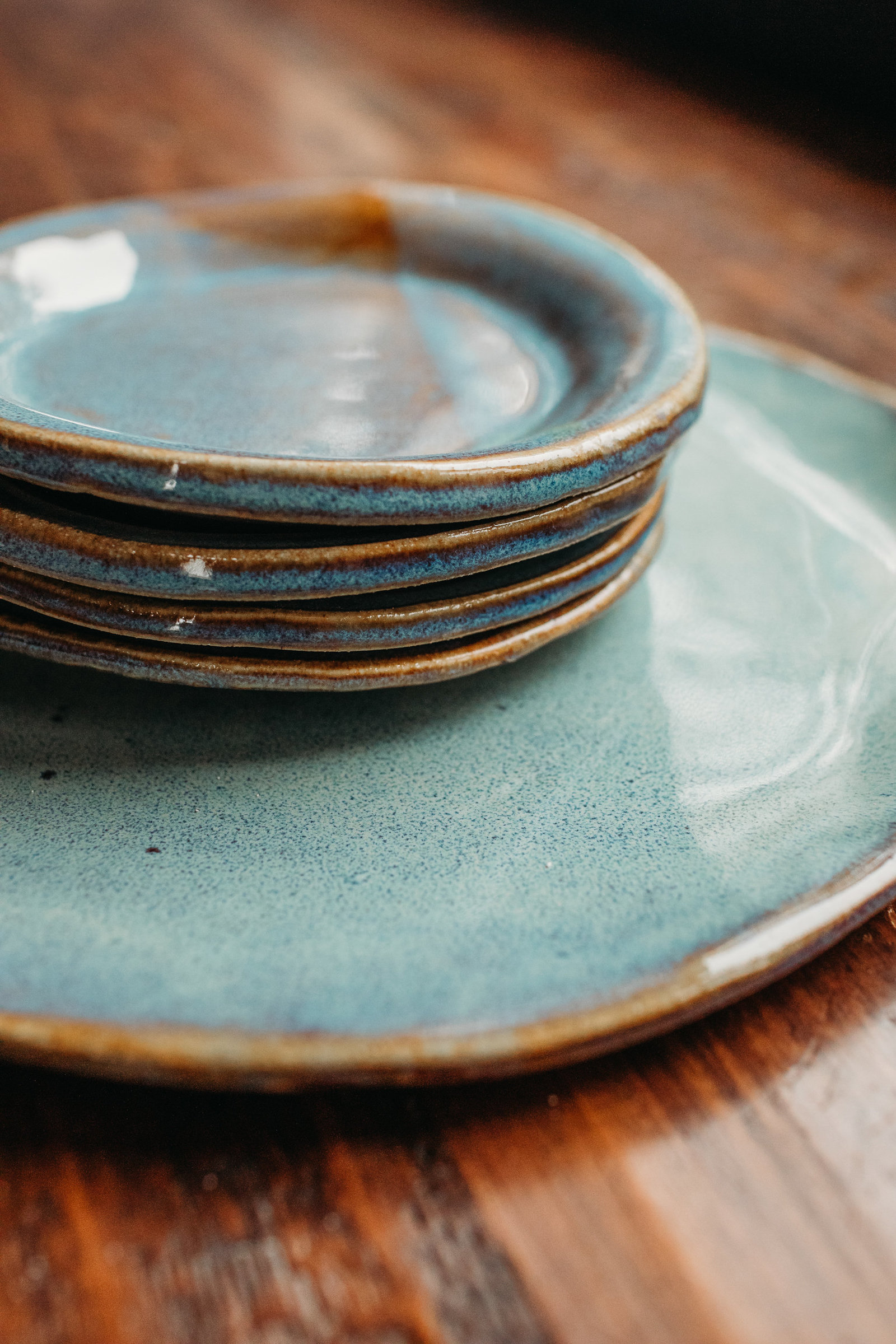 stack of blue pottery dishes with gold edges on a wooden table