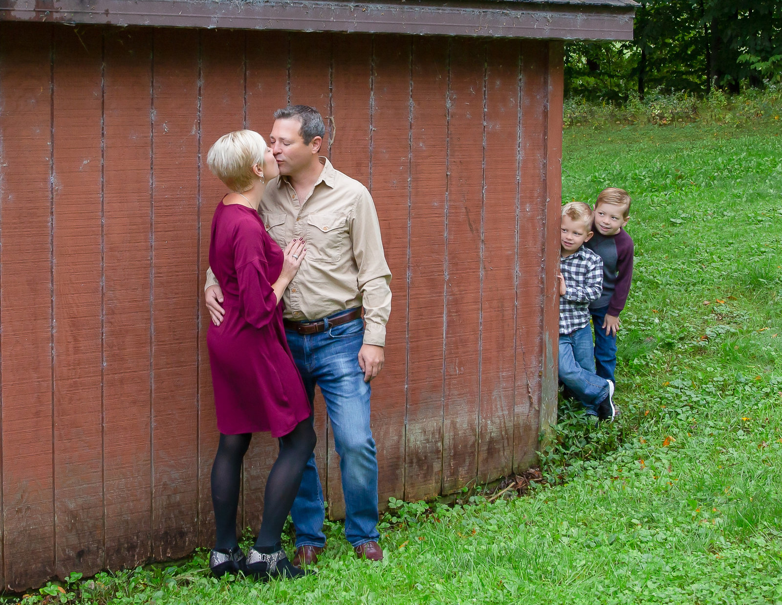 Sweet family posed by a barn.