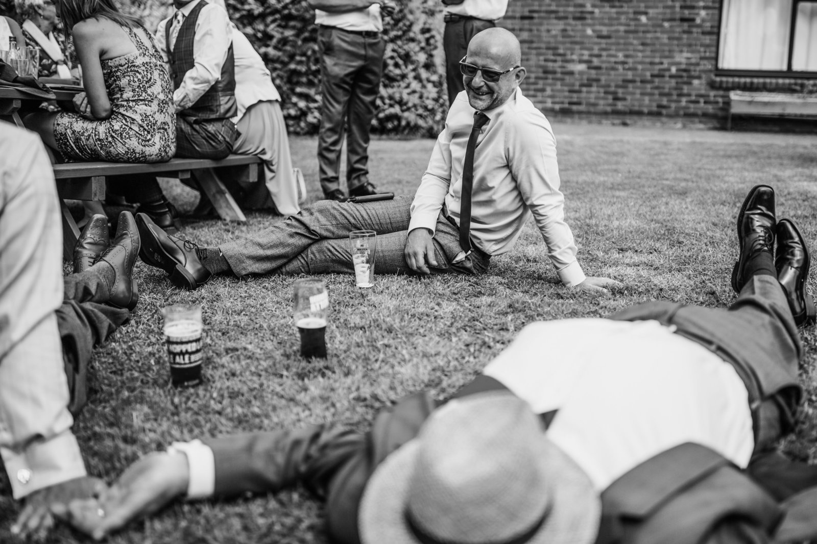 A wedding guest falls asleep on the floor of a Norfolk venue with a hat on his face. Another guest is looking and smiling.