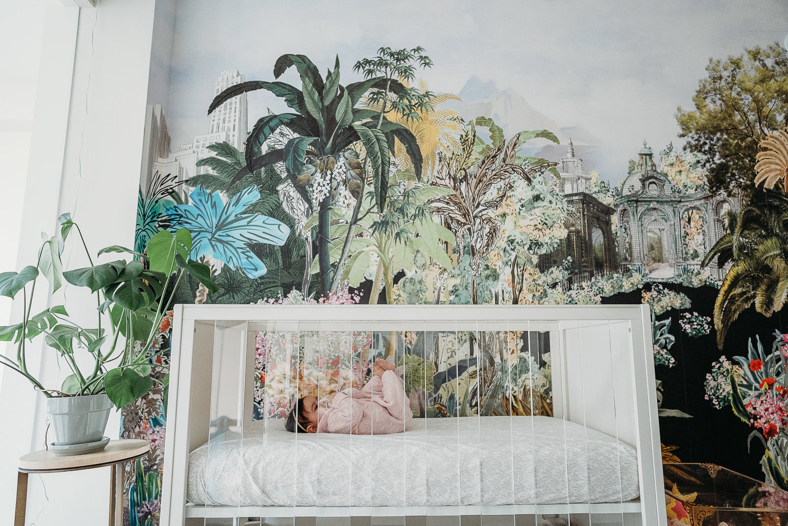 baby girl lies in crib with wall mural during newborn photos in boston mass
