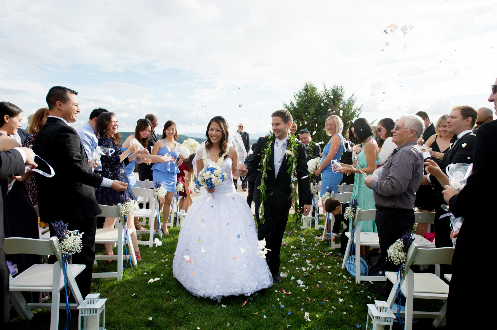 guests throw flowers at bride and groom as they walk down the aisle