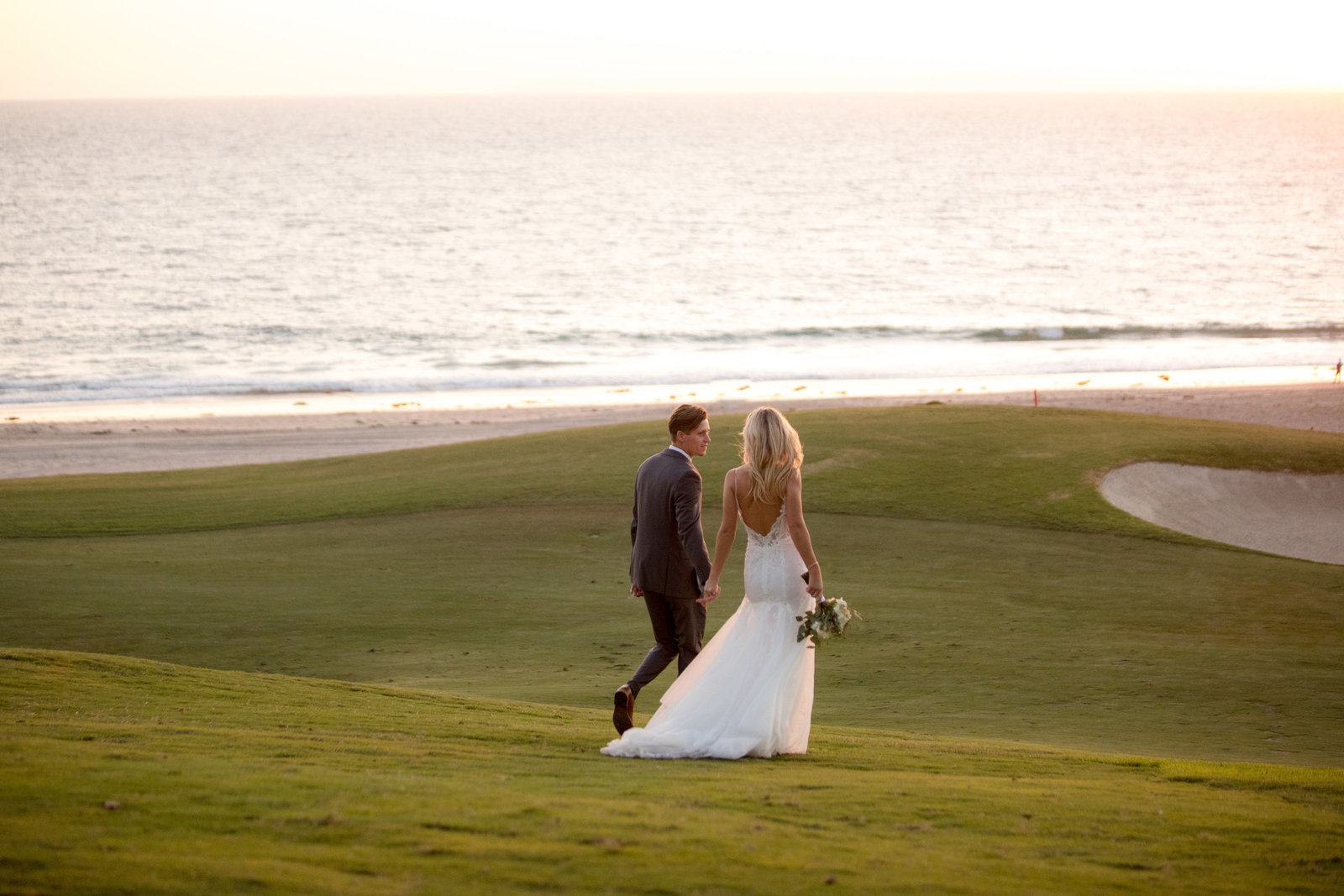bride and groom walking on golf course with beach view