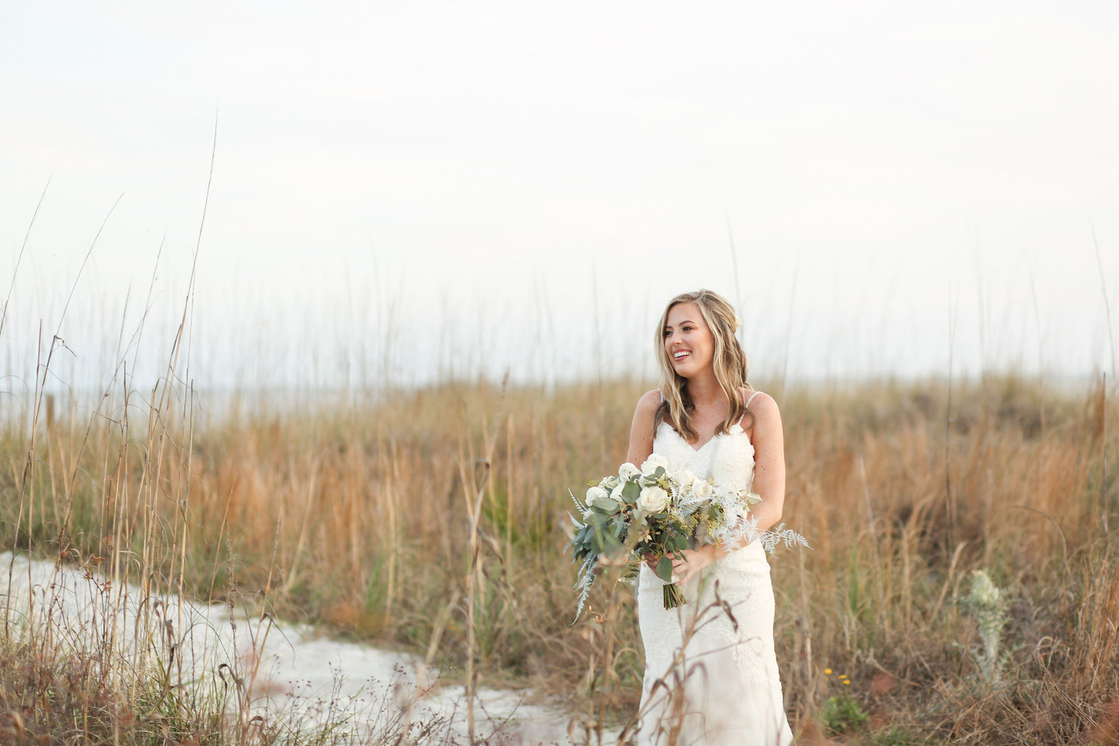 bride standing in grass on beach in hilton head