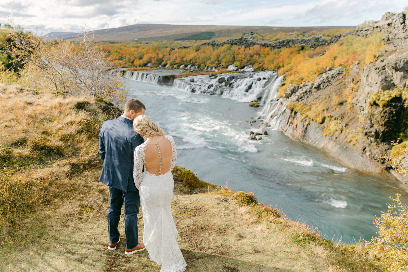 bride and groom with their back to the camera and looking at the waterfalls in iceland