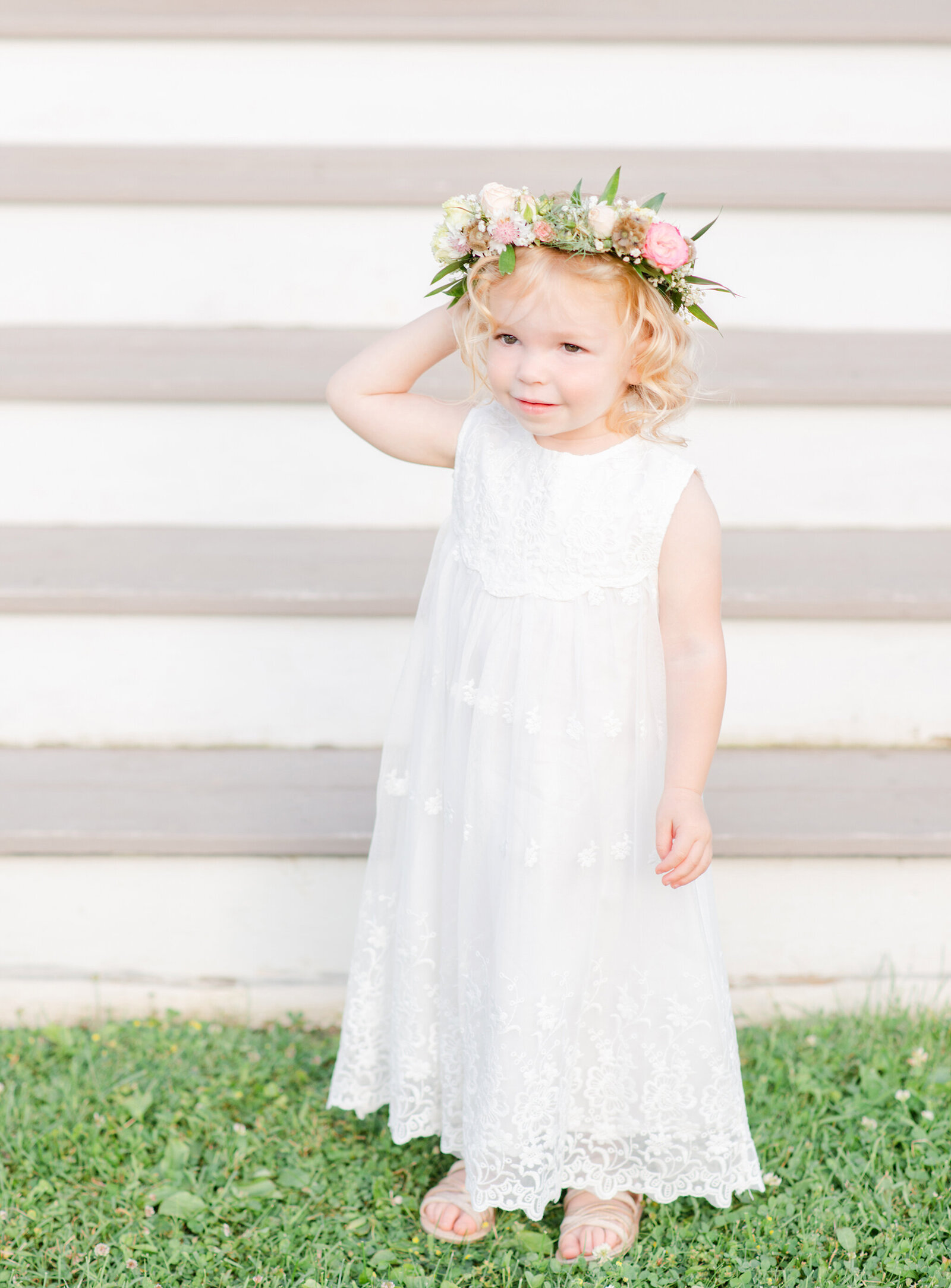 Little girl with floral crown and white dress smiling