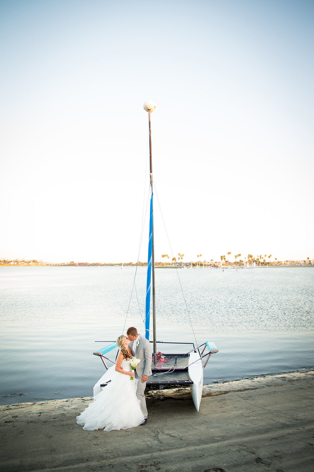 bride and groom with sailboat catamaran