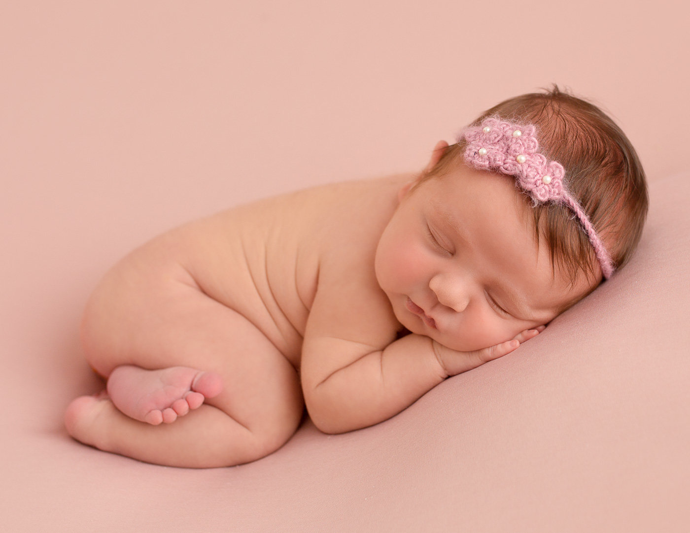 Beautiful newborn girl in bum up pose in our Rochester, NY studio.