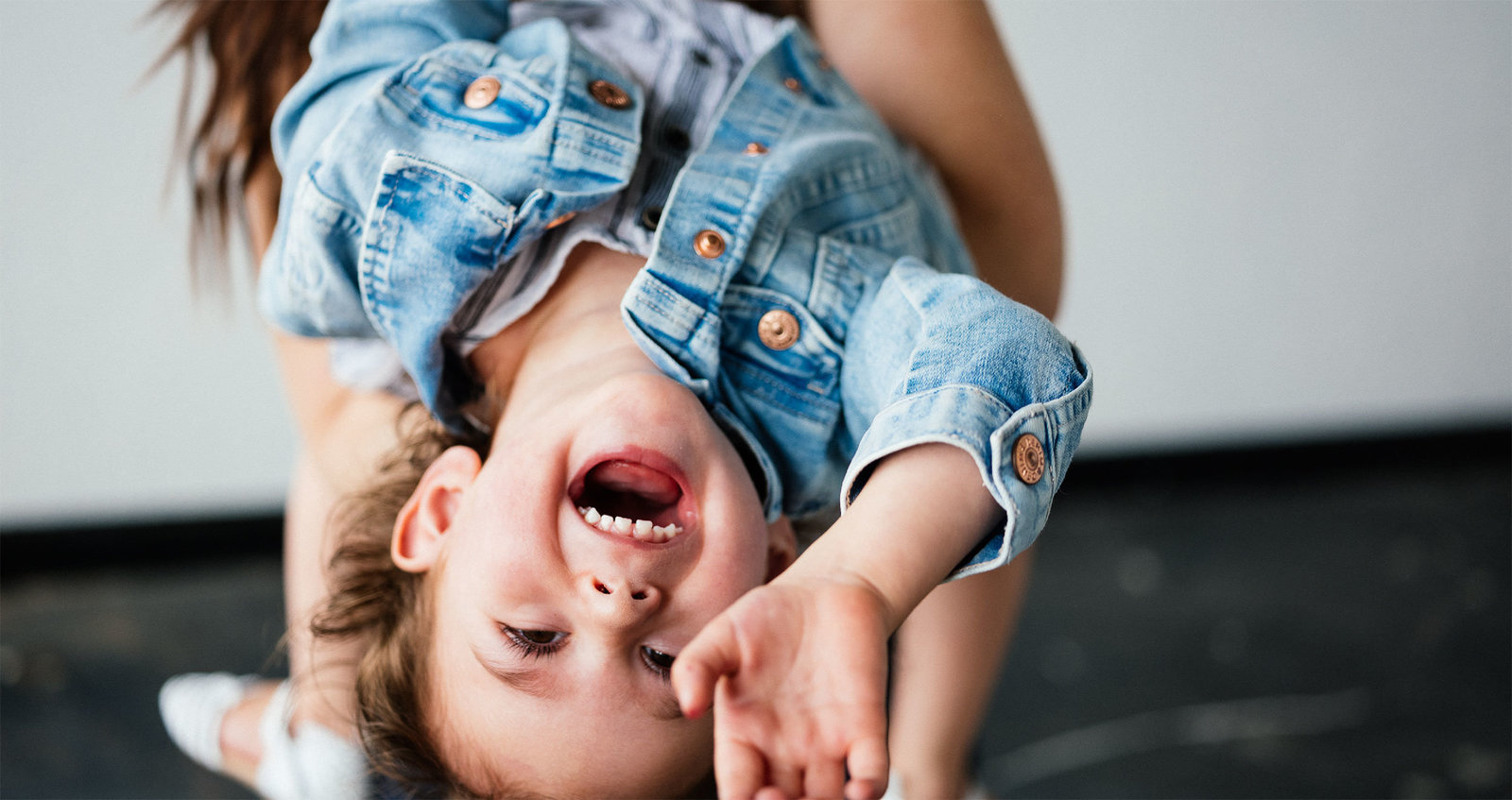 toddler girl hanging upside down with a joyful expression