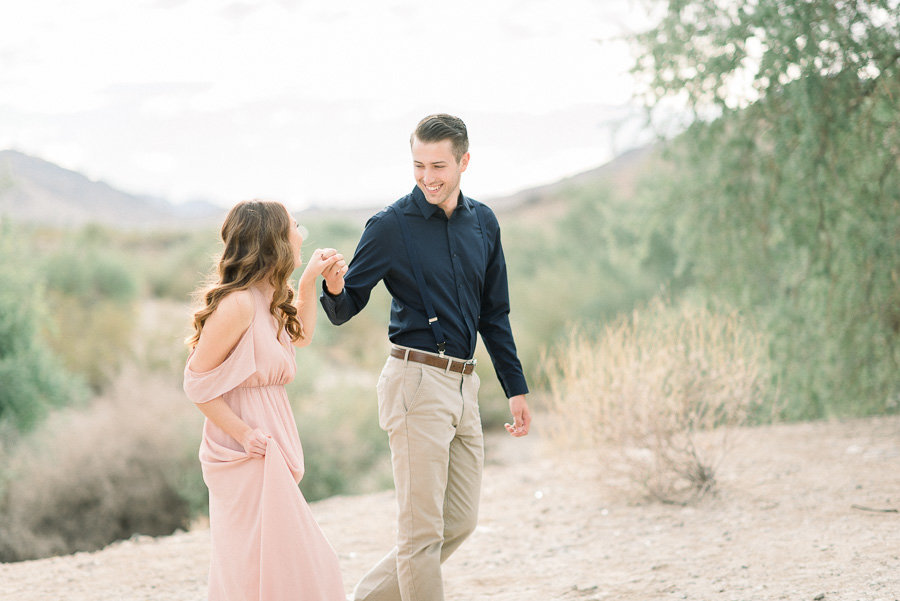 Tucson Desert Engagement Session Photo of Couple Wearing Blush Pink Gown and Navy Blue Shirt Walking Side By Side | Tucson Wedding Photographer | West End Photography
