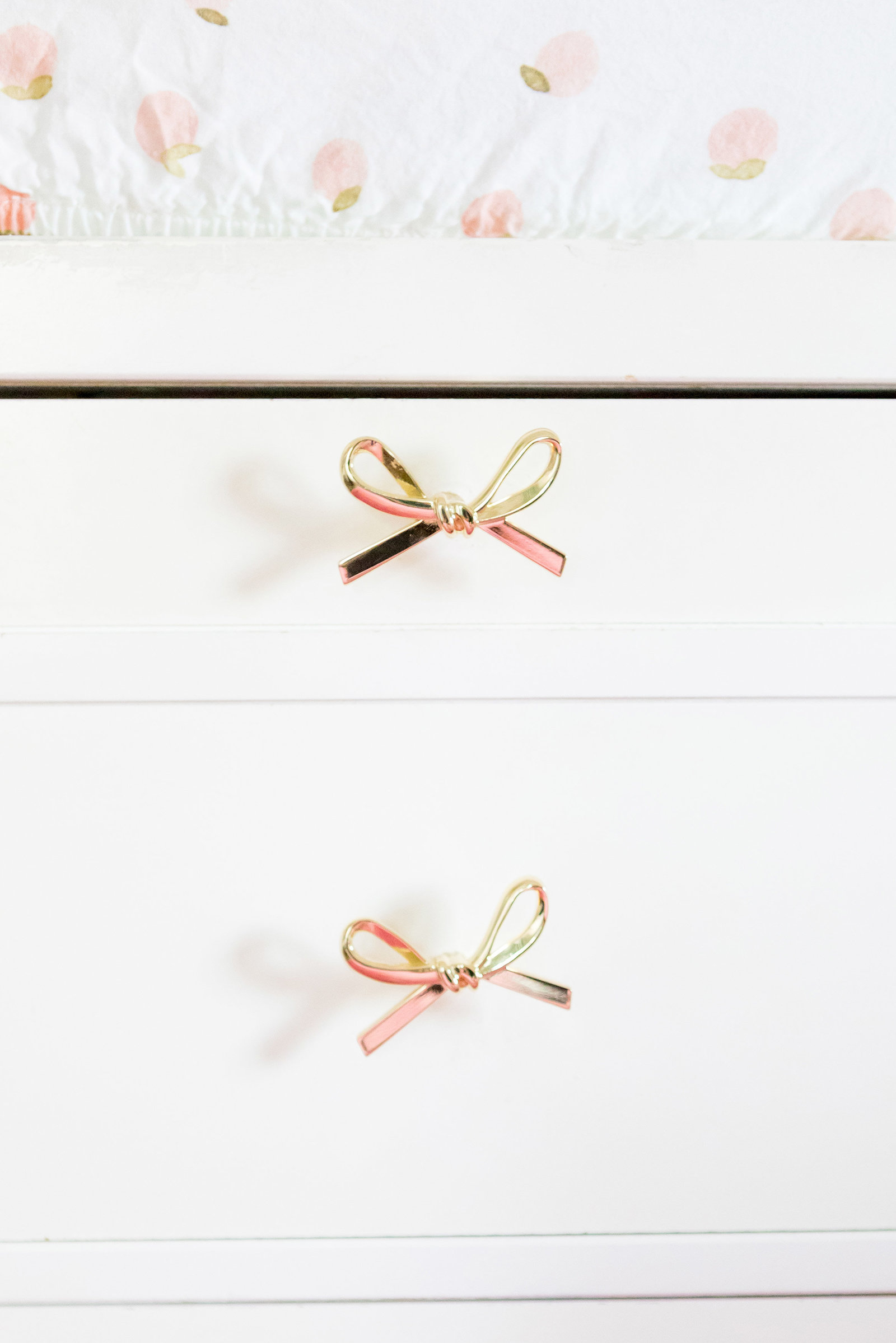 A white dresser changing table with rose gold bow pulls.