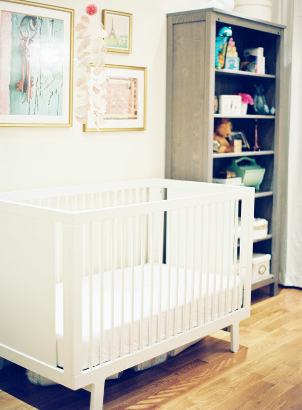 A nursery with a white crib, three wall hangings, and decorated bookcase.