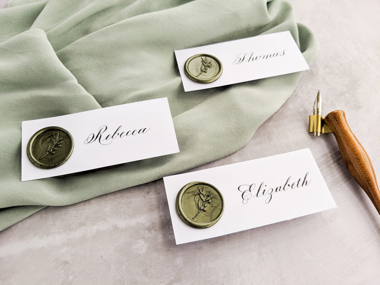 Copperplate calligraphy place cards with olive green wax seal