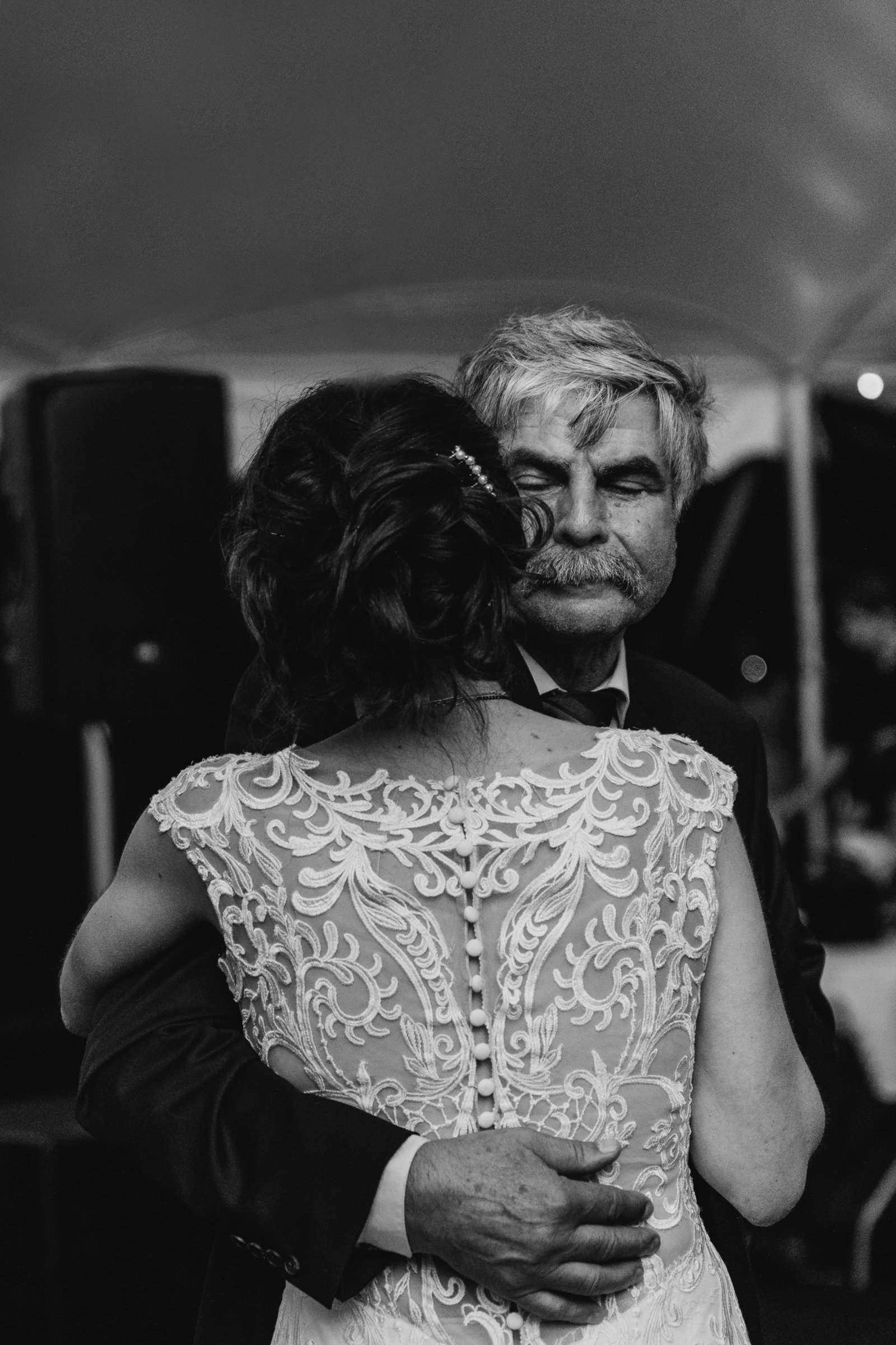 father of the bride dances with daughter wearing lace backed dress at wedding