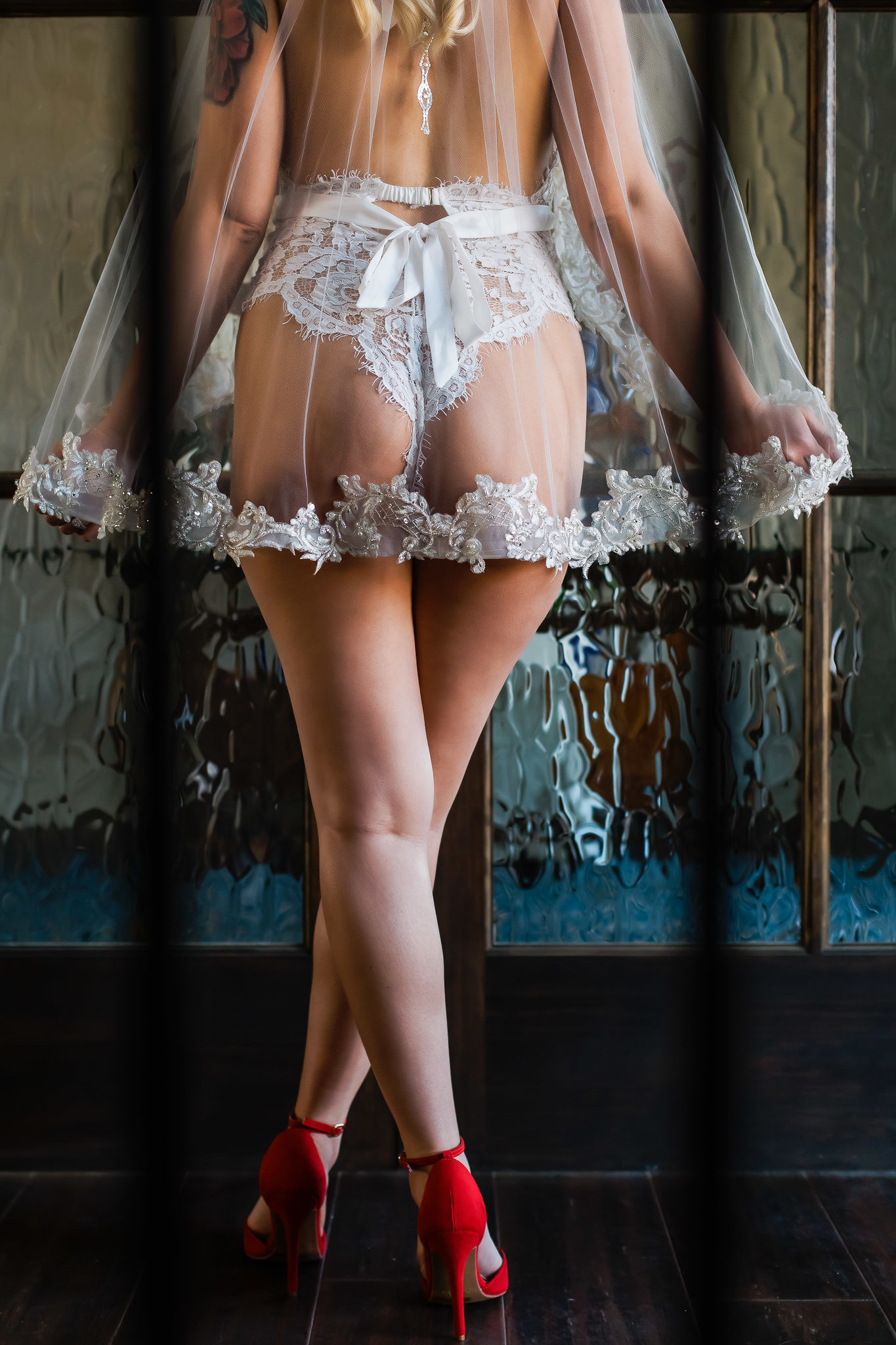 Boudoir photo of a bride wearing a veil and red high heels