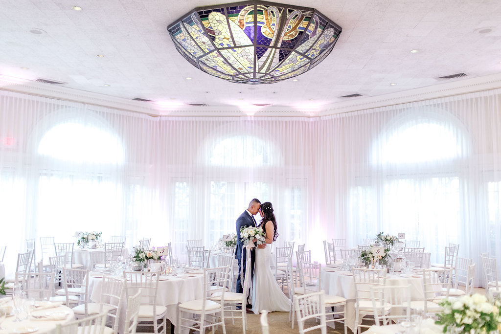 Couple shares a moment in the Pavilion surrounded by their decorated guest tables and Vizcaya's custom stain-glass chandelier.