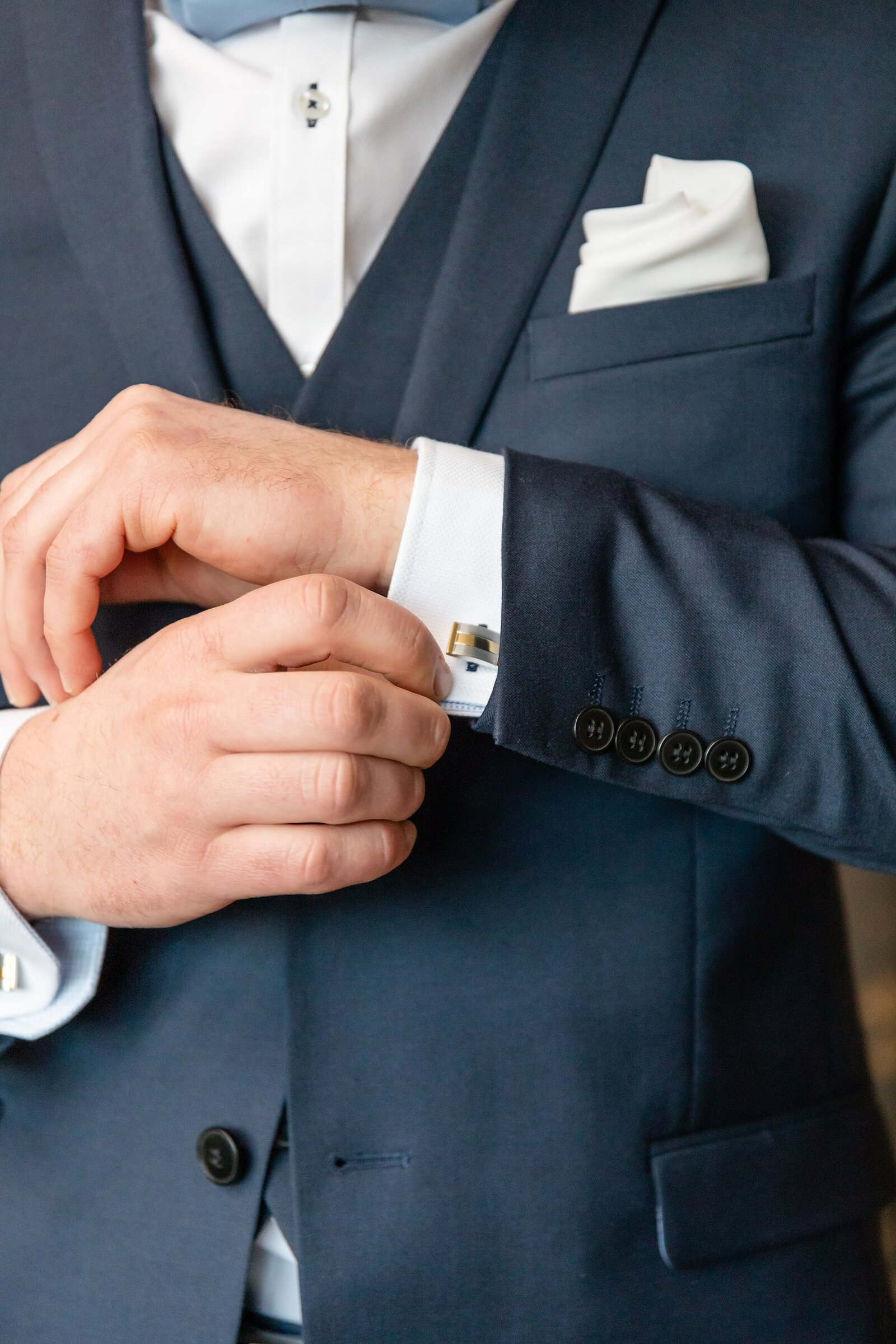 Groom-adjusts-the-cufflinks-as-he-gets-ready-to-see-his-bride