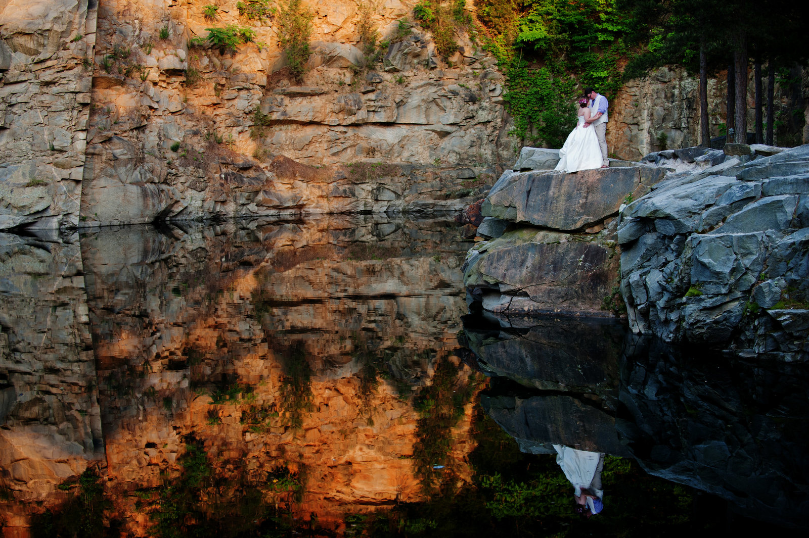 couple kiss on edge of rock with reflection in water