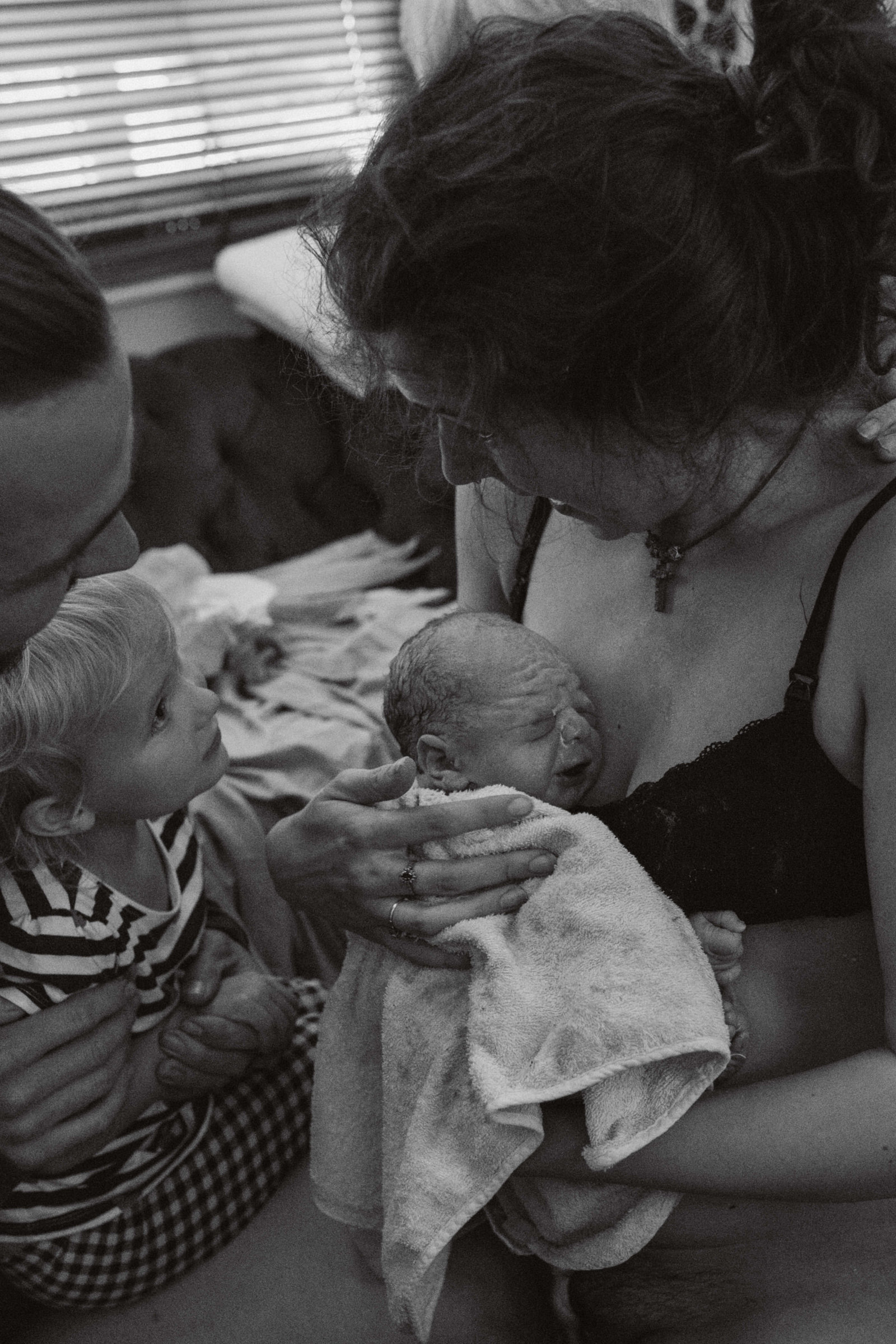 Black and white Documentary photograph of Ipswich mum holding newborn baby seconds after home birth