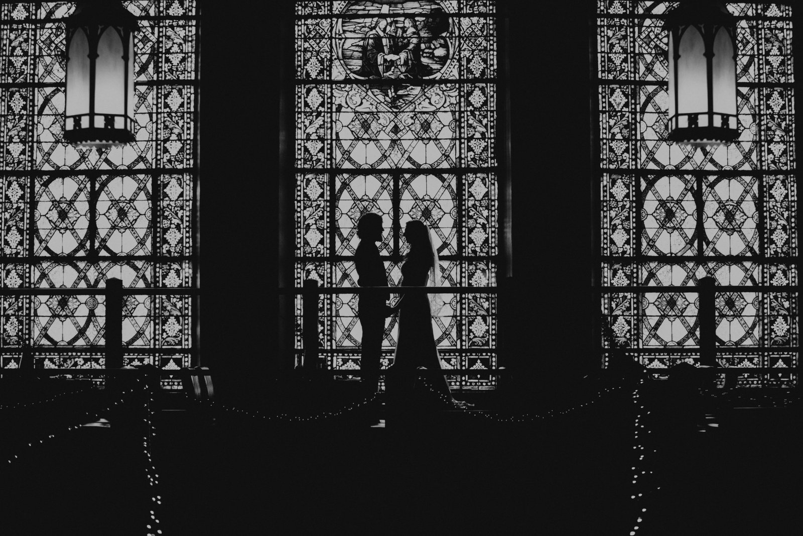 The Bluestone wedding photos silhouette of a bride and groom in front of large stained glass windows