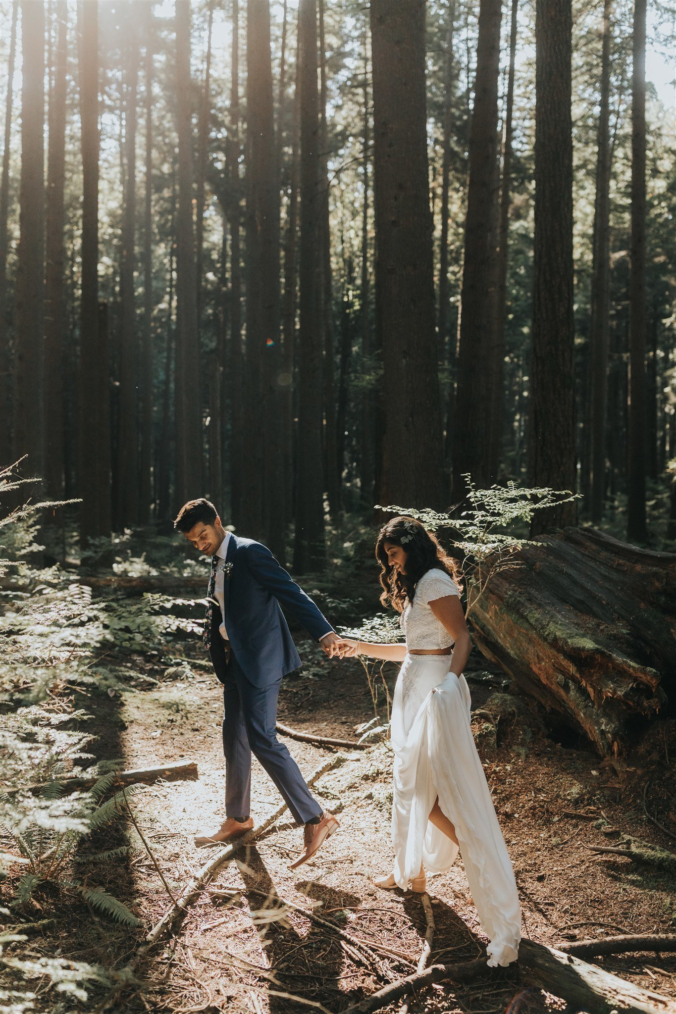 bride and groom walking through magical forest light