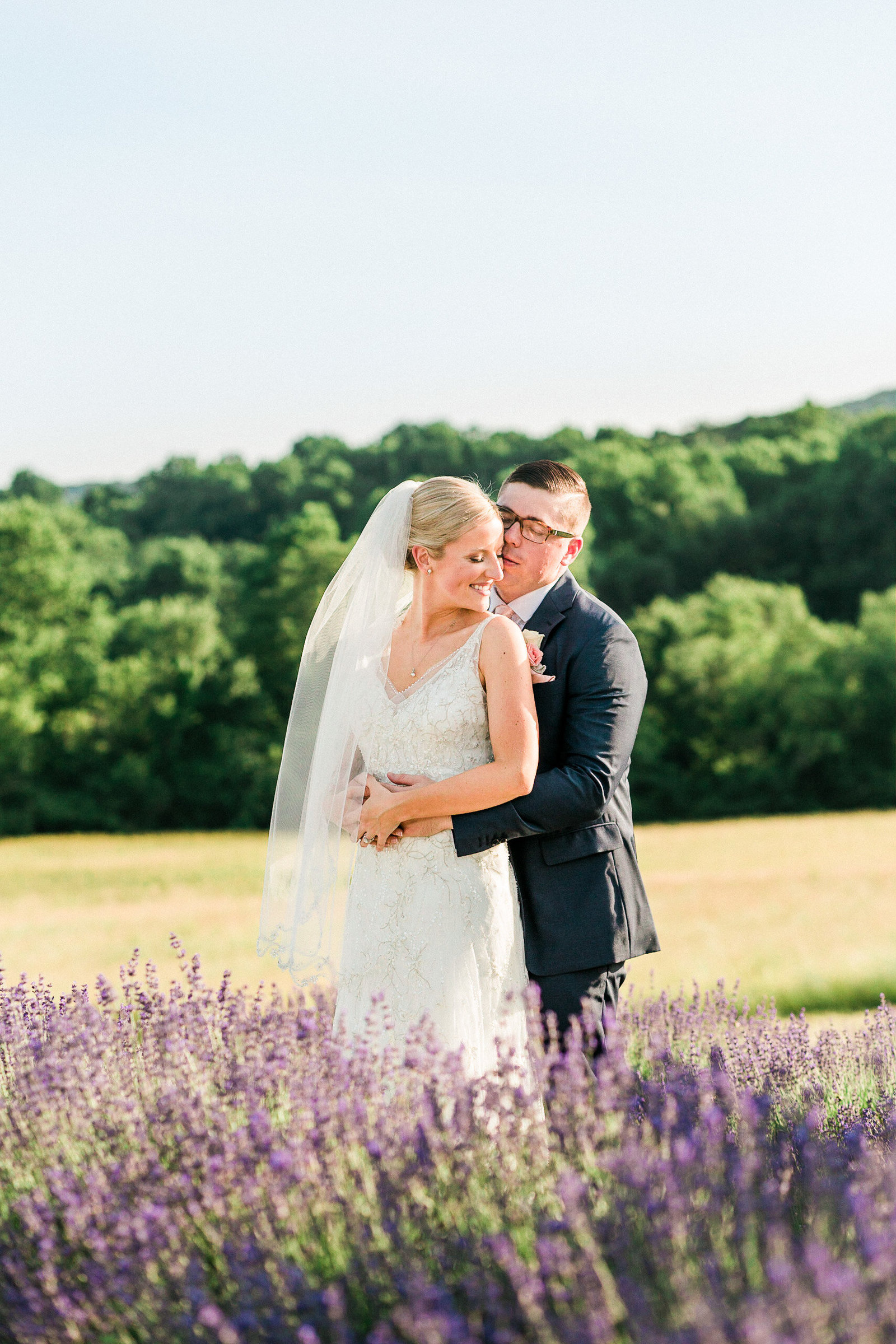 Bride and groom standing in a lavender filed on a sunny day at springfield manor maryland
