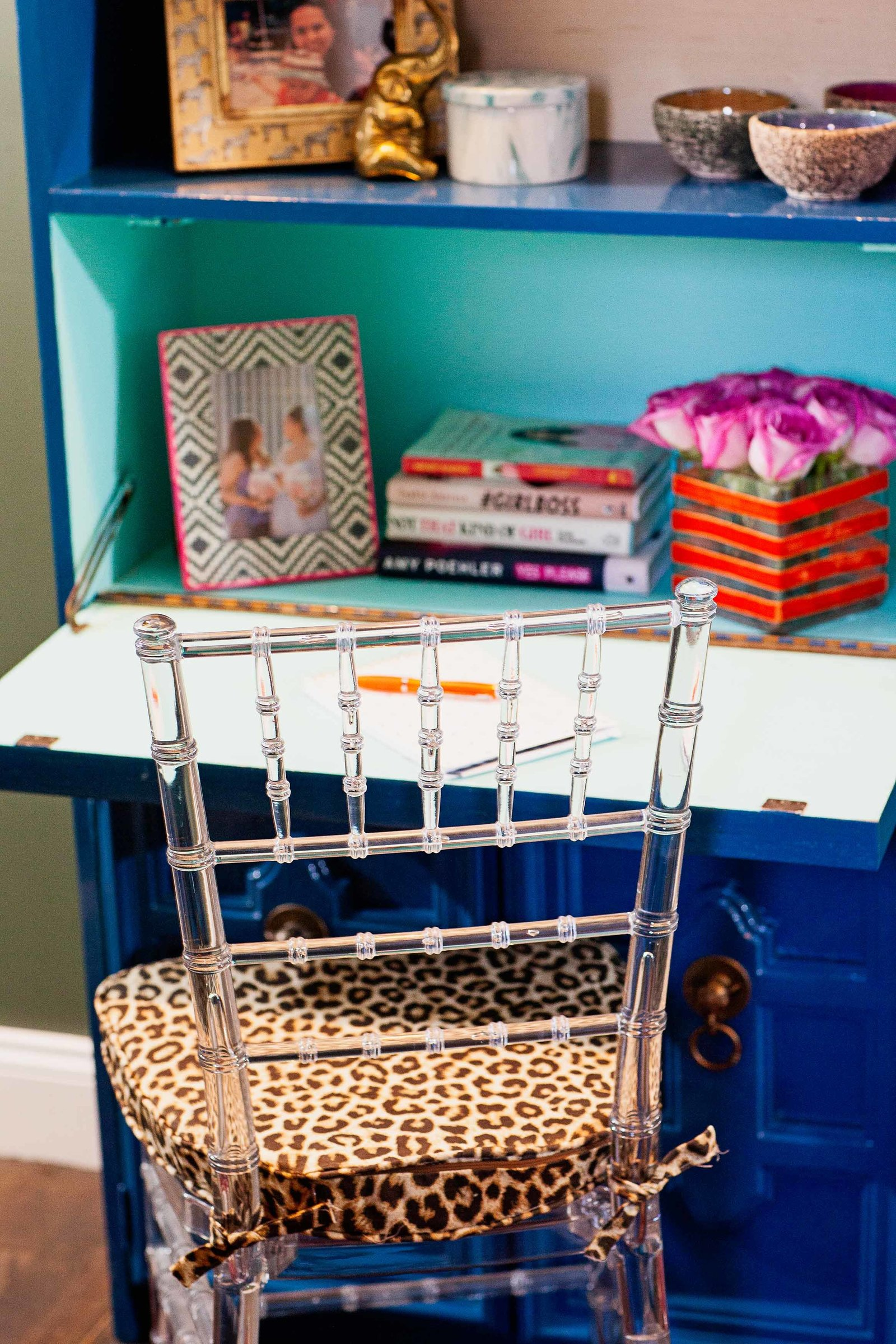 A blue writing desk with a clear acrylic chair and leopard print cushion.