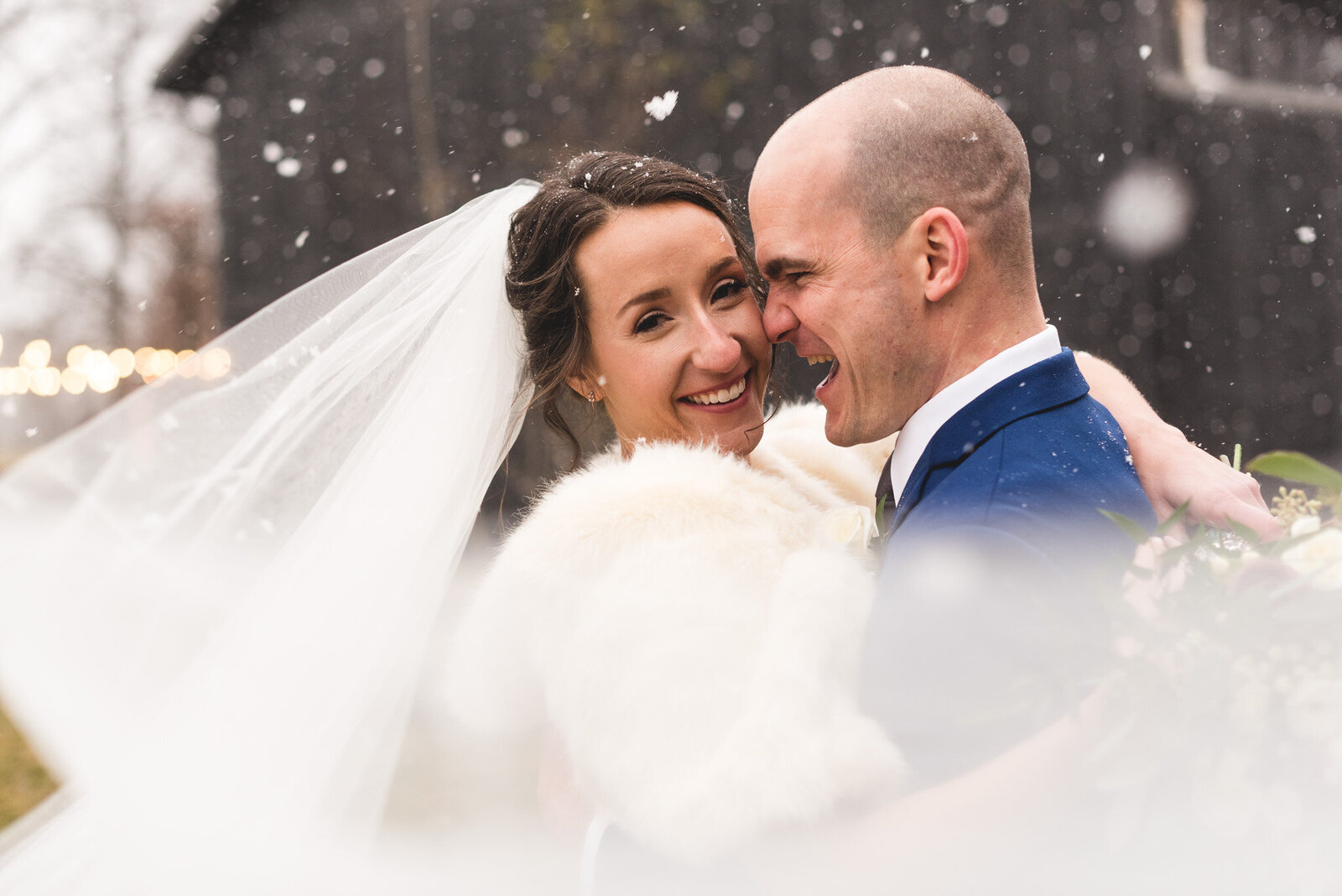 bride-and-groom-laughing-in-snow-at-barn-wedding-jorgensen-ohio